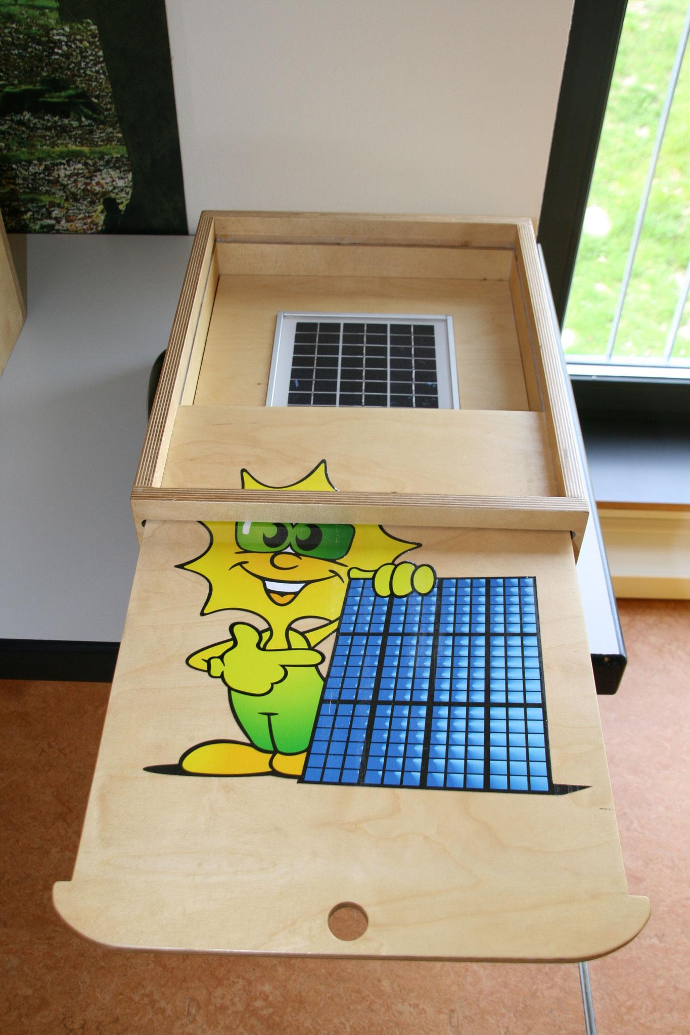 Nach Öffnen des Deckels fällt Licht auf die Solarzellen. Die Energie wird als Pfeiffton dargestellt.