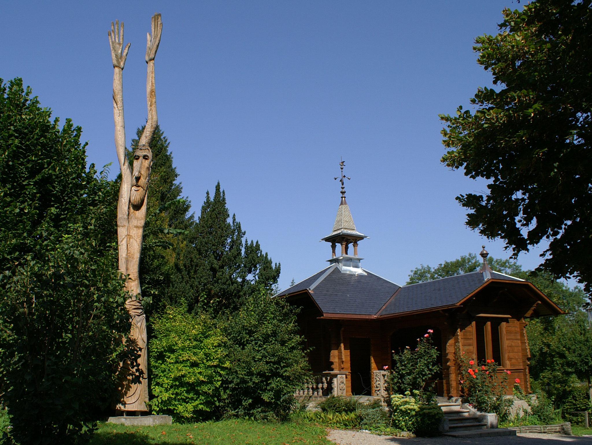 """Das Gartenchalet kurz nach der Restaurierung, mit Skulptur """"Lothar"""" von J.U. Steiger"""