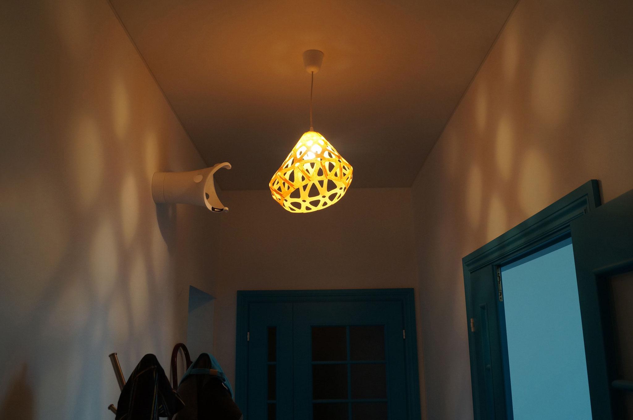 Невероятные световые пятна на стенах от желтого подвесного светильника ZAHA LIGHT в холле дизайнерской квартиры.