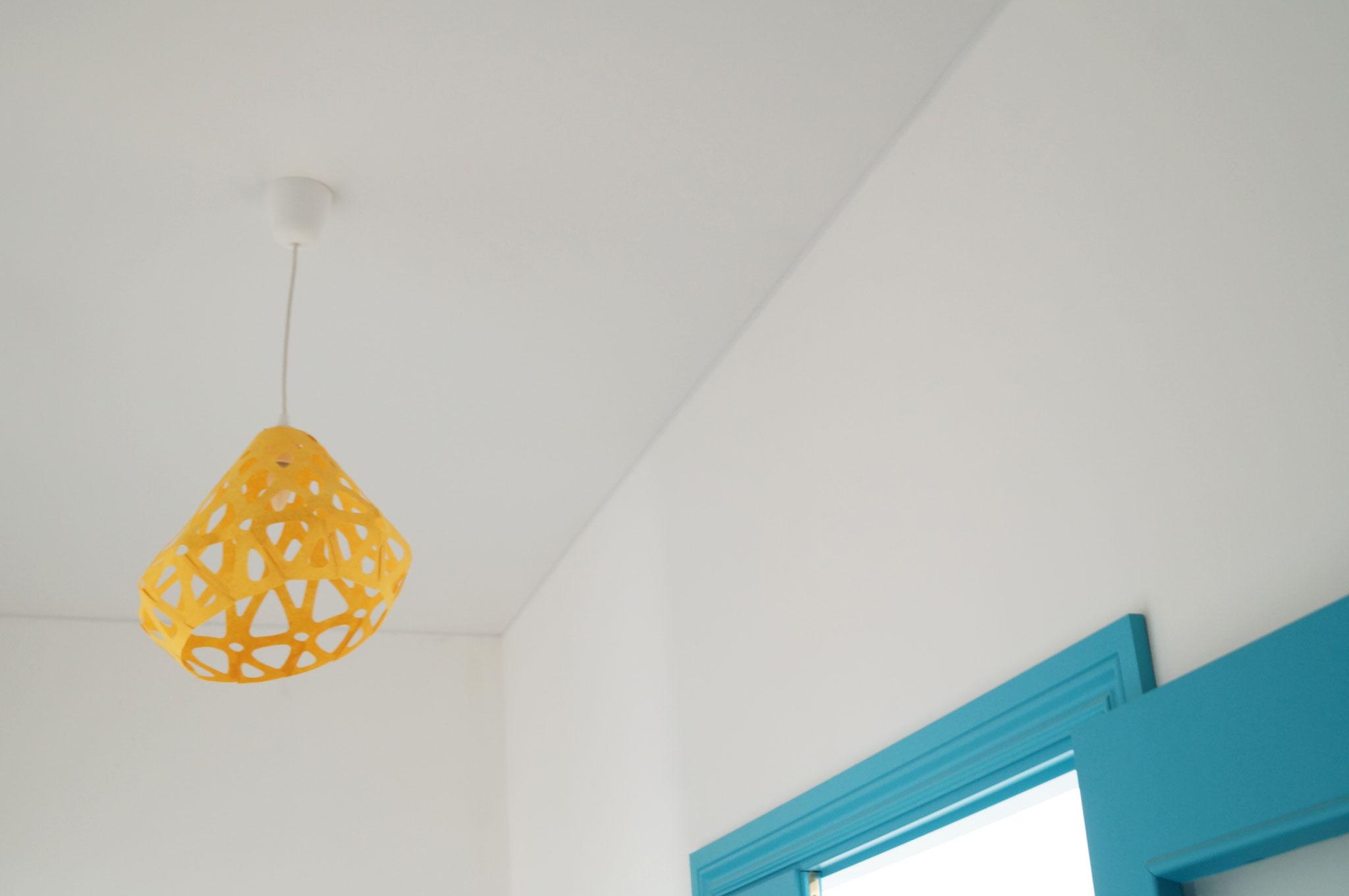 Яркий желтый подвесной светильник ZAHA LIGHT в прихожей квартиры с ярко голубыми цветами.