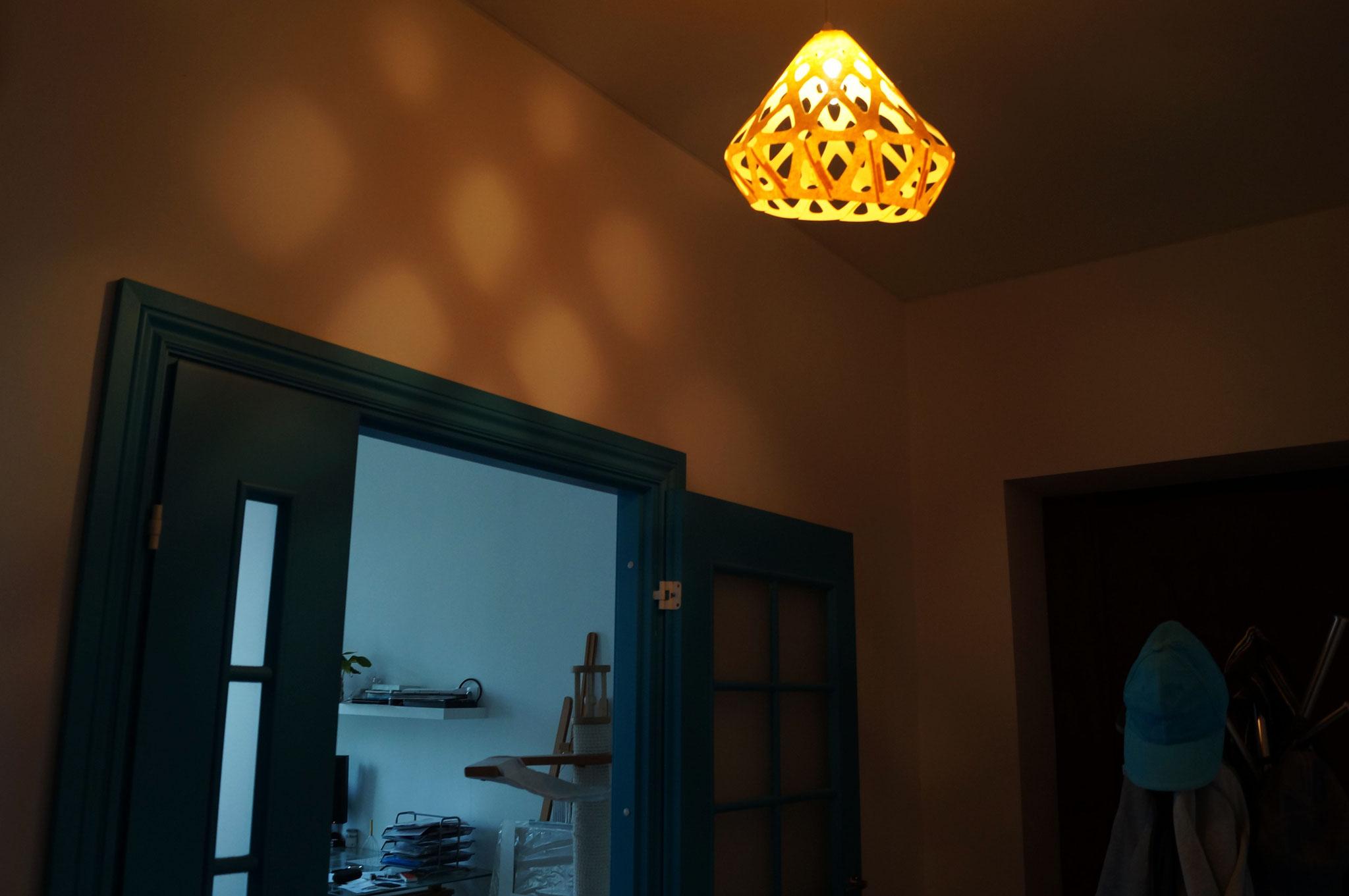 Желтый подвесной светильник ZAHA LIGHT в прихожей делает невероятные узоры на стене.