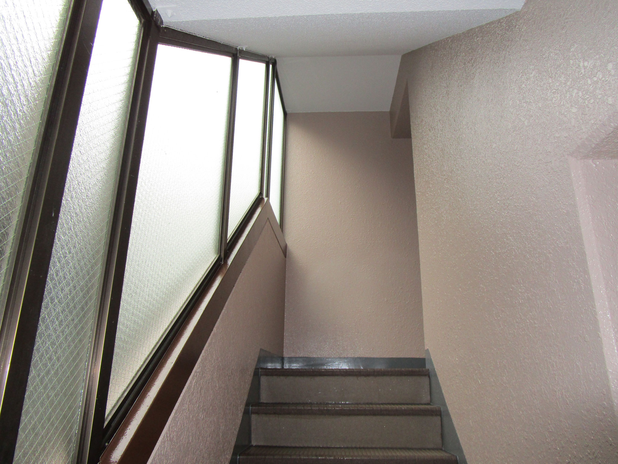 共用の階段部分。天井はホワイト系、壁の色はシャンパン・手すり部分はセピア色です
