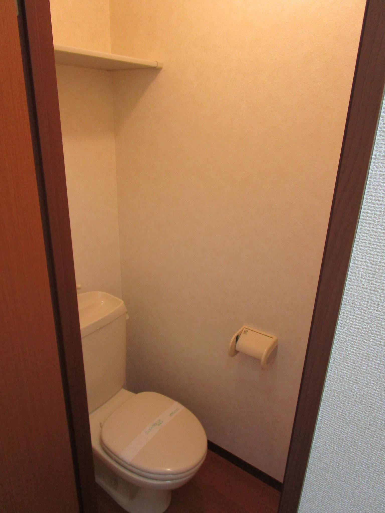 玄関を入って廊下の左側のトイレ。上部に棚付き