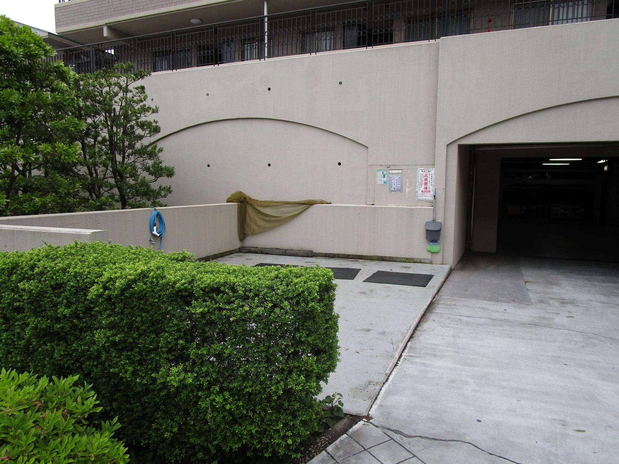 管理棟の隣の駐車場入口。向かって左側はゴミ置き場