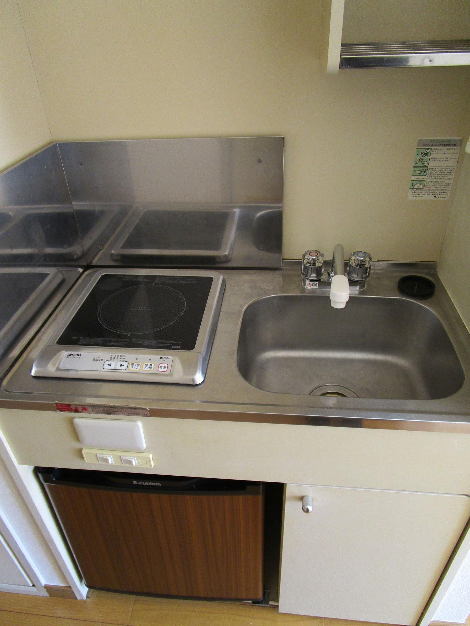 その隣はキッチン。木目調のミニ冷蔵庫付き