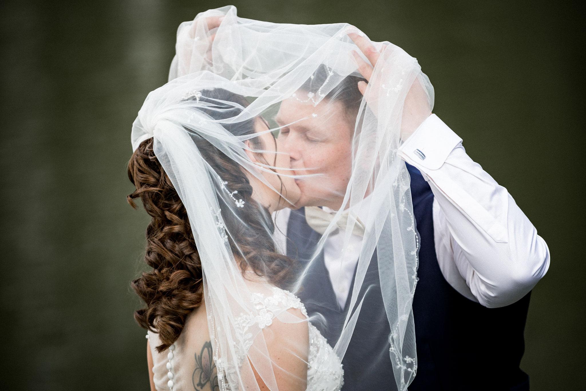 Bräutigam küsst Braut unterm Schleier