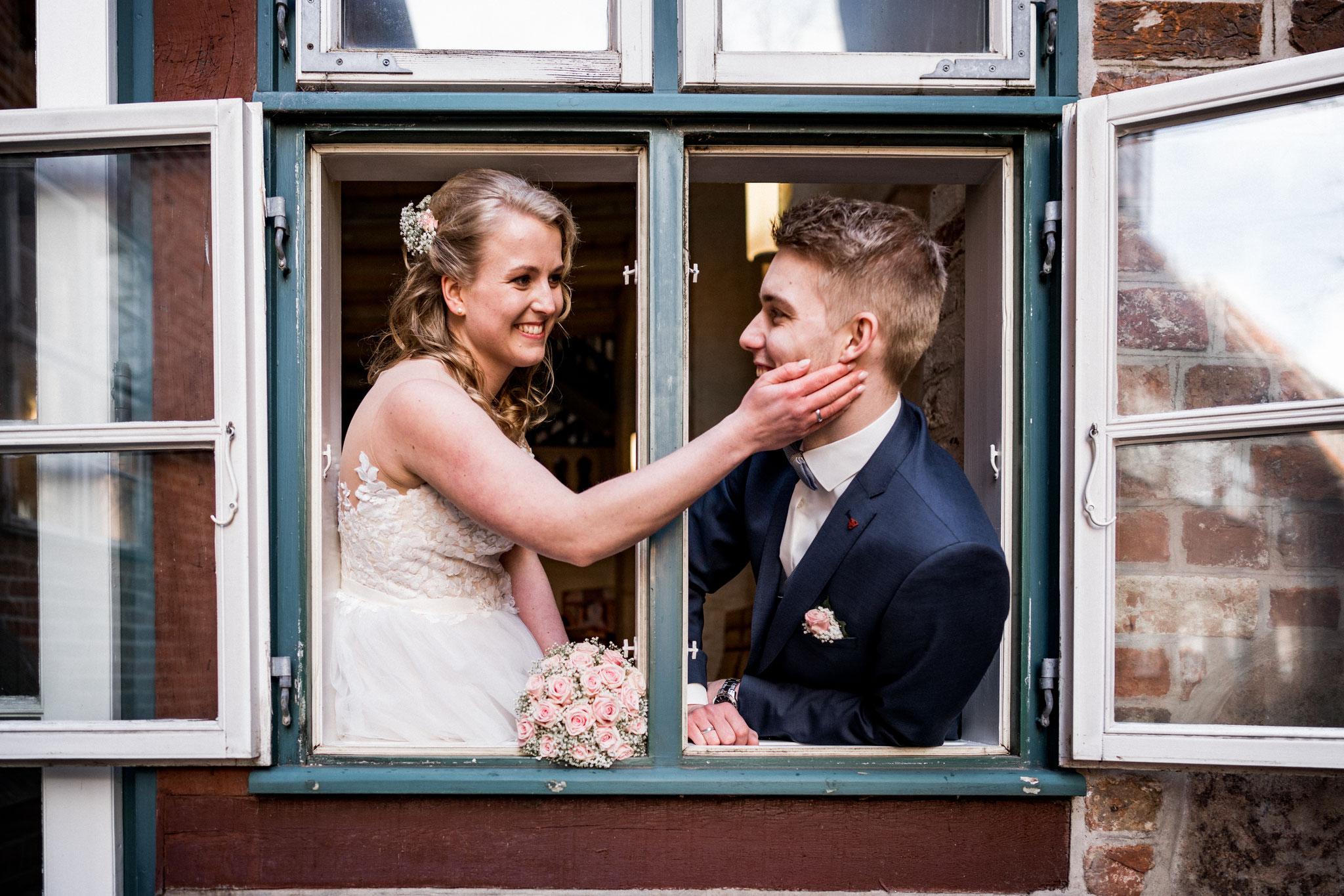 Brautpaar am Fenster beim Brautpaarshooting