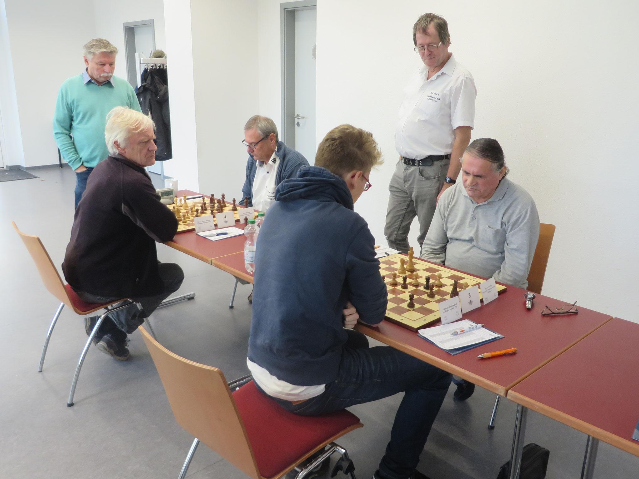 Olaf und Helmut sind schon fertig und gucken sich die noch laufenden anderen beiden Partien an Brett 3 und 4 an
