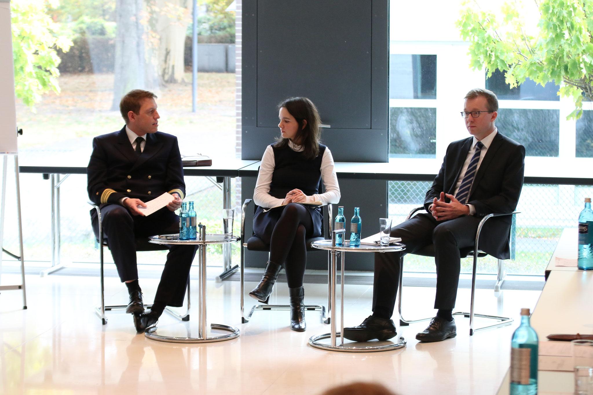 Juliane Kabus im Gespräch mit Sebastian Hoffmeister (BMI) und Dr. Patrick Jungkunz (BMVg).