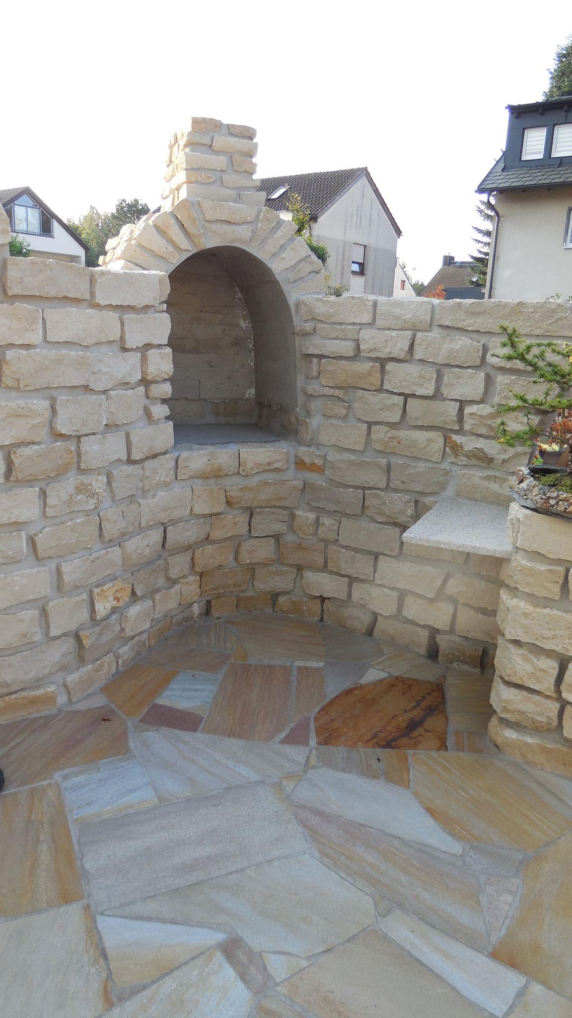 Sichtschutzmauer aus Naturstein mit integriertem Grill