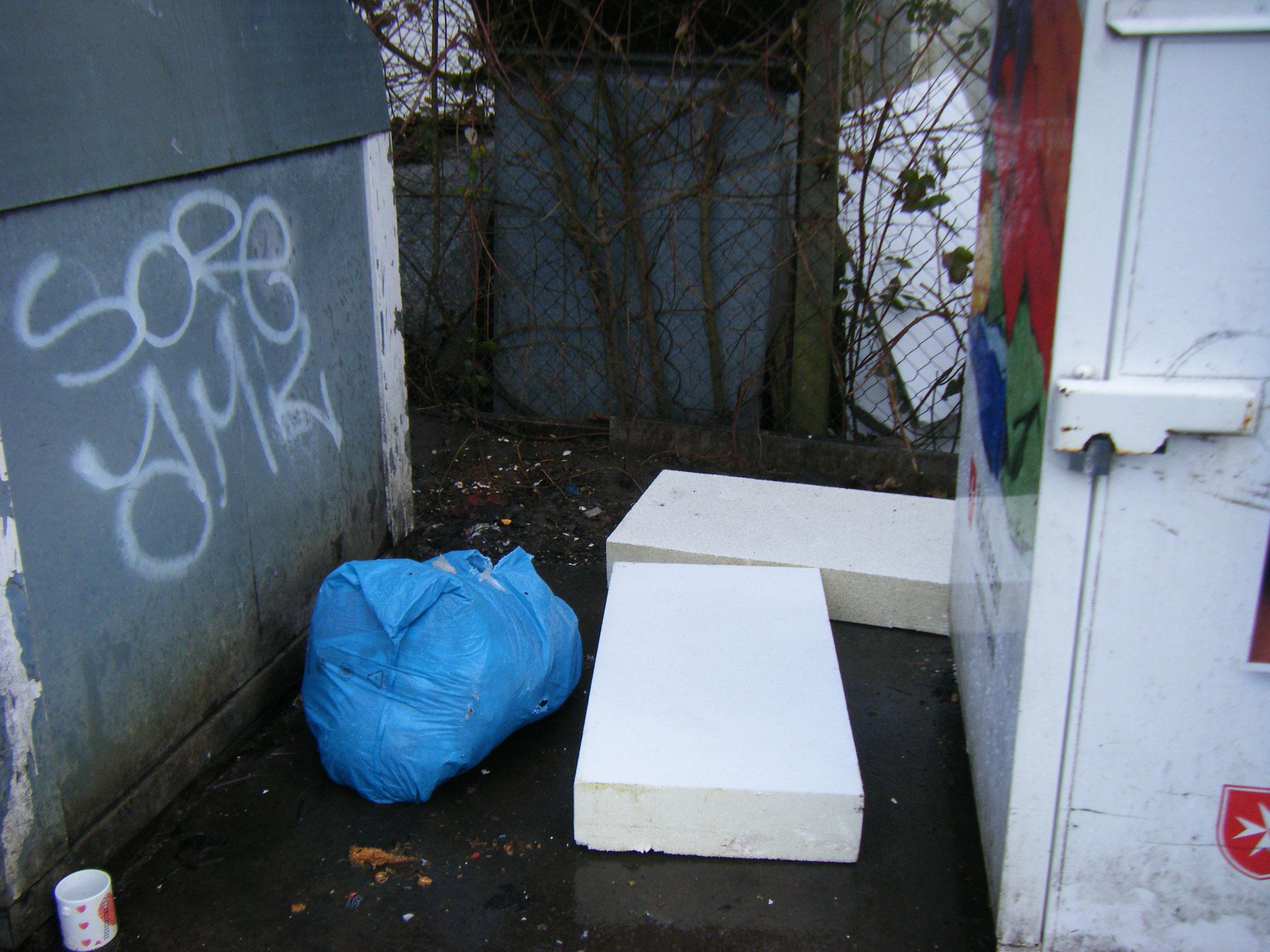 umherfliegende Styroporteile landen in Nischen neben aufgerissenen Müllsäcken