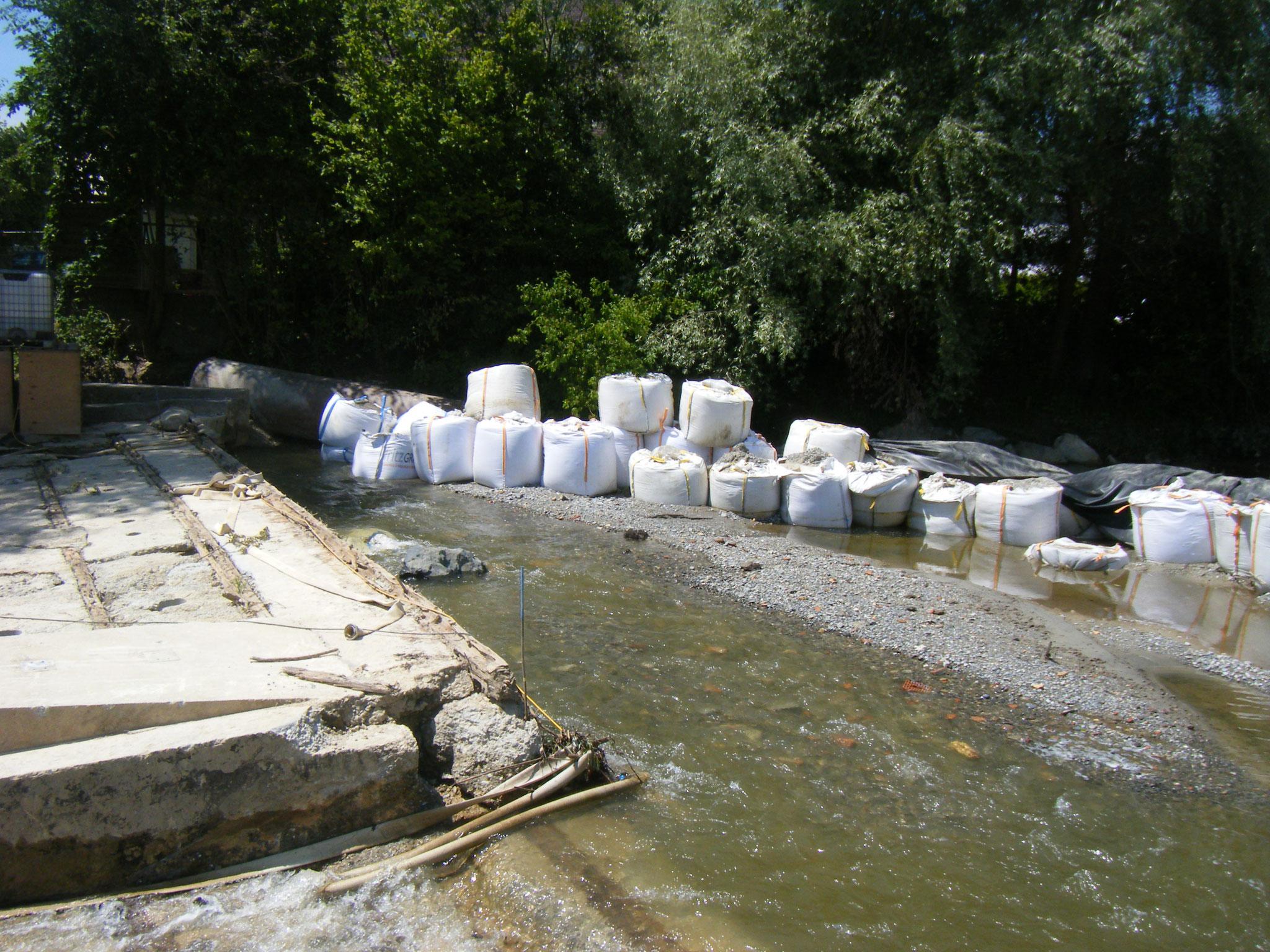 die Hälfte des Flusswassers hat sich einen Weg unter dem Stahlrohr im Hintergrund gebahnt