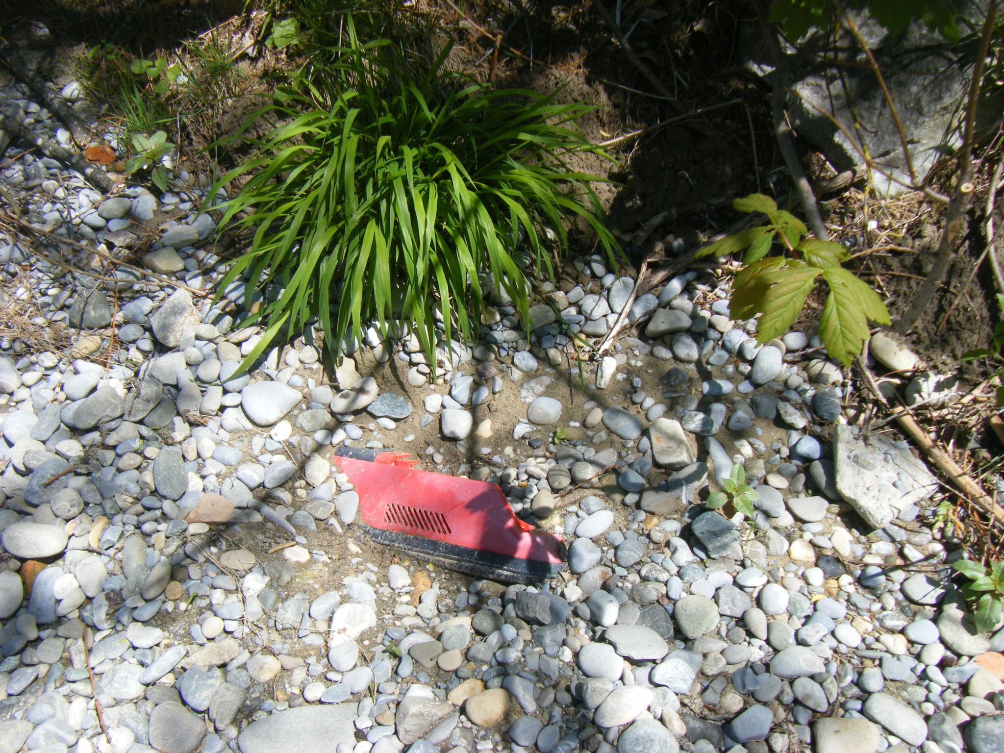 ein Stück weiter vorne lag ein undefinierbares rotes Maschinenteil halb im Kies verborgen