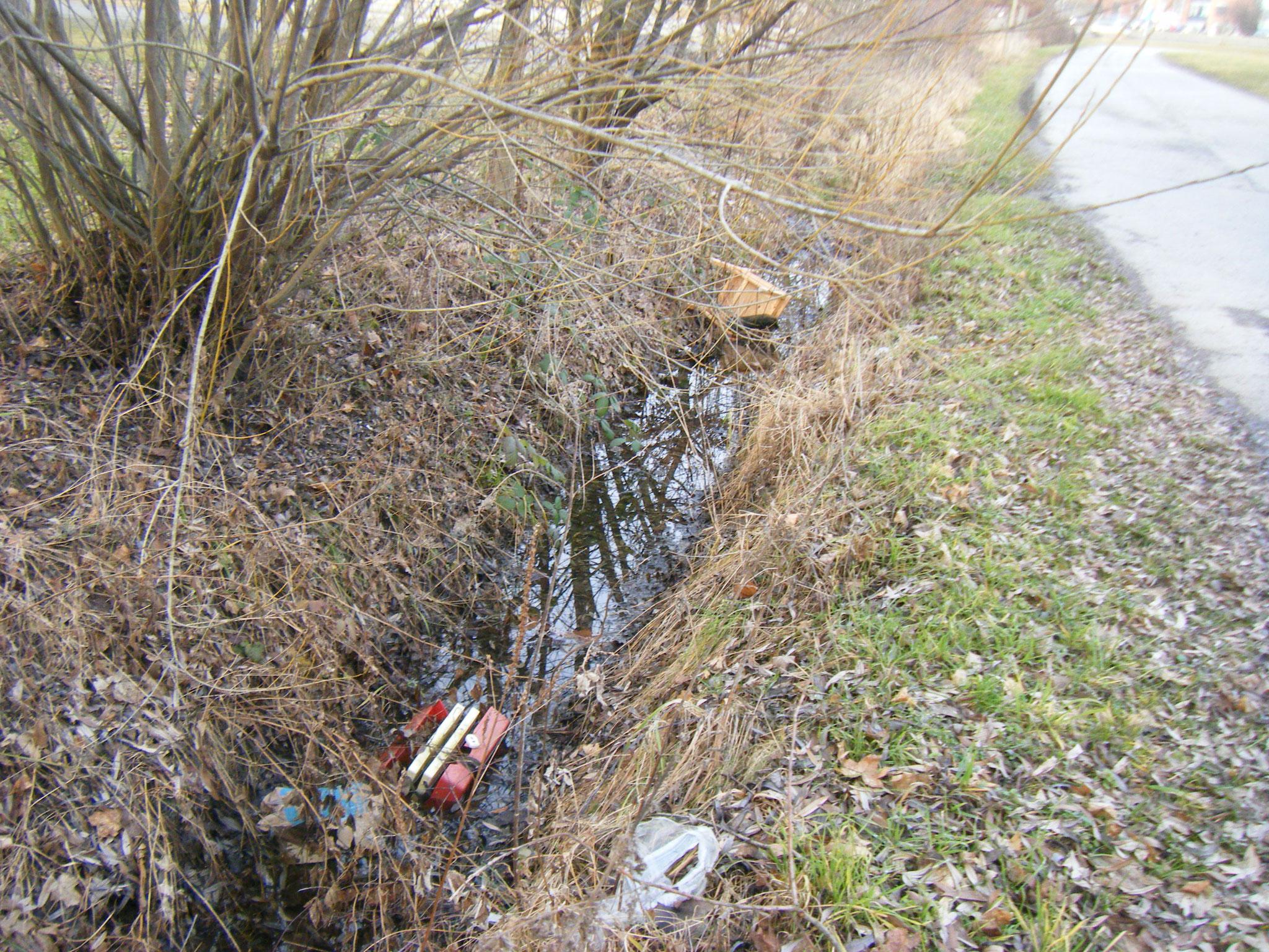 im Abwassergraben auf dem P7-Parkplatz: Sperrmüll, ein Stuhl und ein Plastik-Werkzeugkoffer