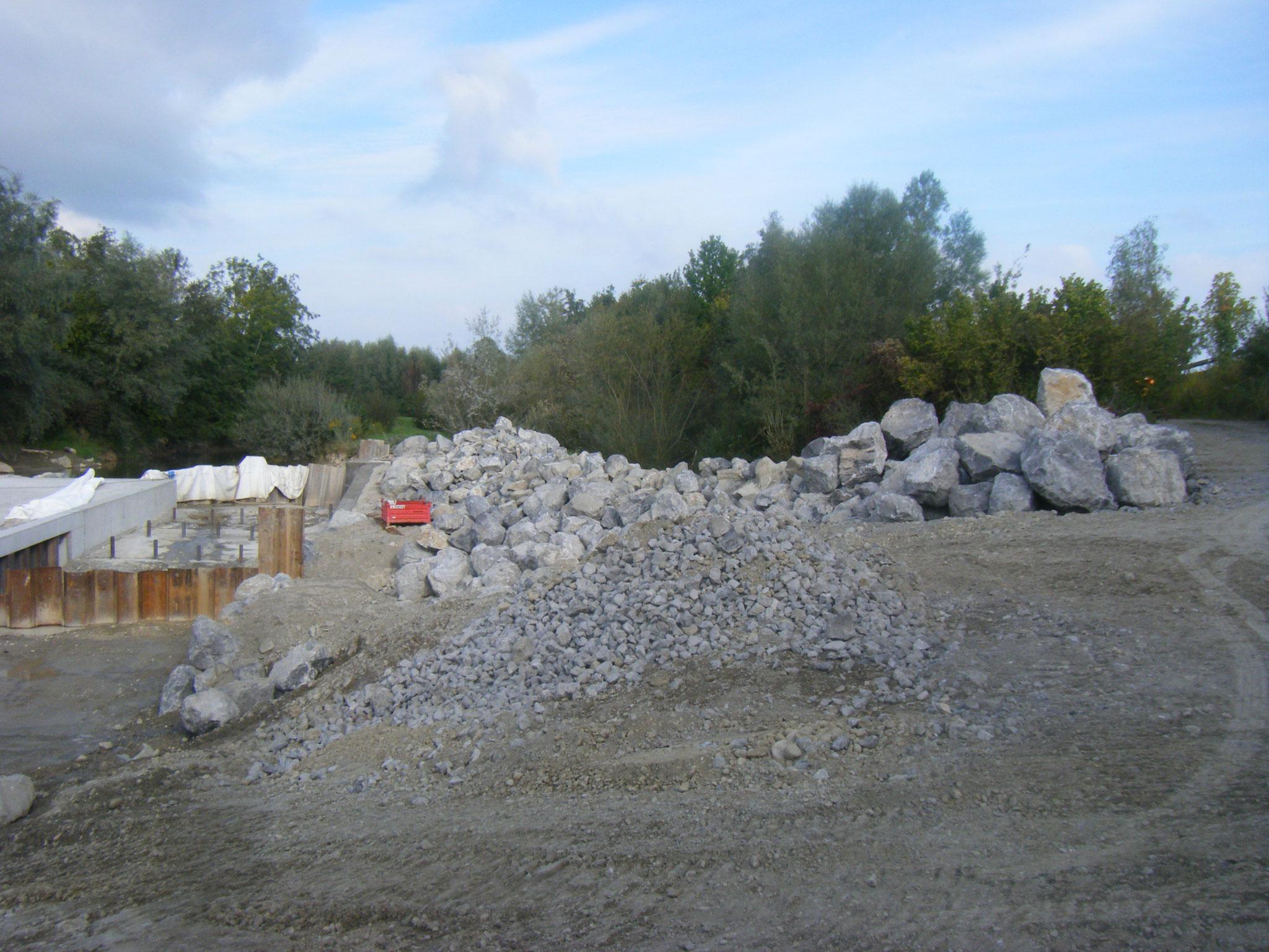 Ein großer Wall von Steinen sichert den Damm zwischen Baustelle und Rotach/Allmannsweiler Bach