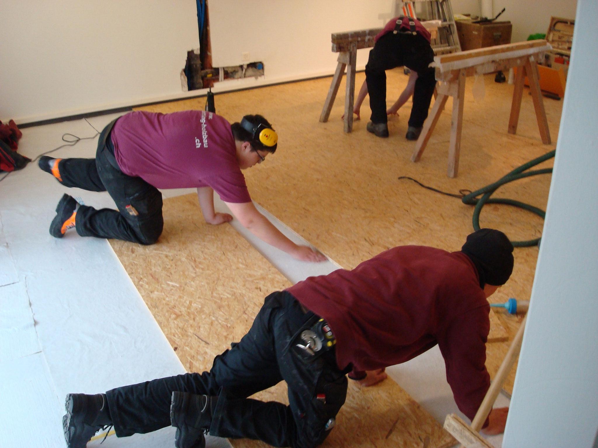 Die Lernenden von Dettling Holzbau beim Einbauen des Werkstattbodens.