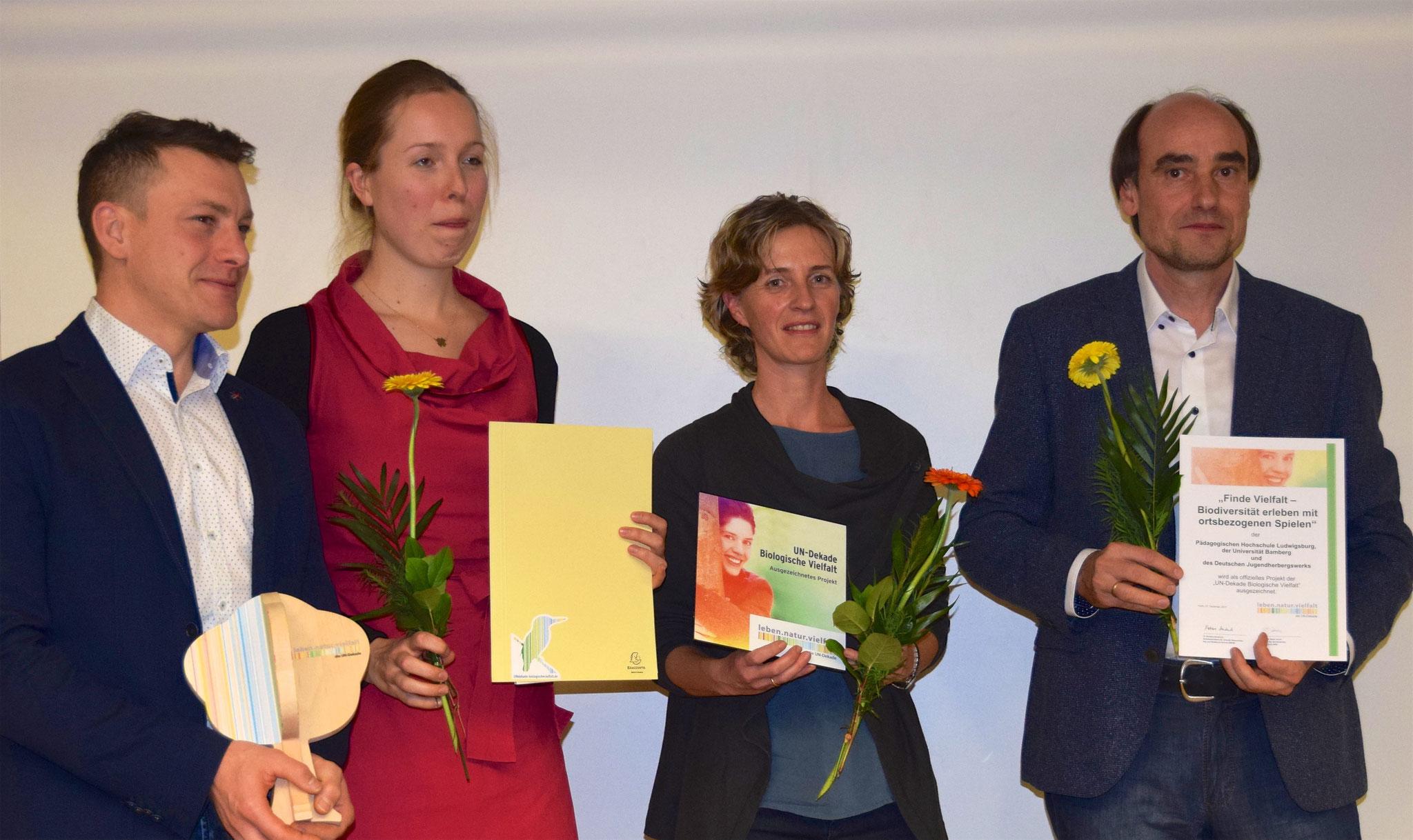 Das gesamte Projekt-Team der PH Ludwigsburg Prof. Dr. Steffen Schaal, Anabel Haas, Dr. Sonja Schaal und Prof. Dr. Armin Lude mit dem Baum der UN-Dekade und Urkunde. Foto: Projekt Finde Vielfalt.