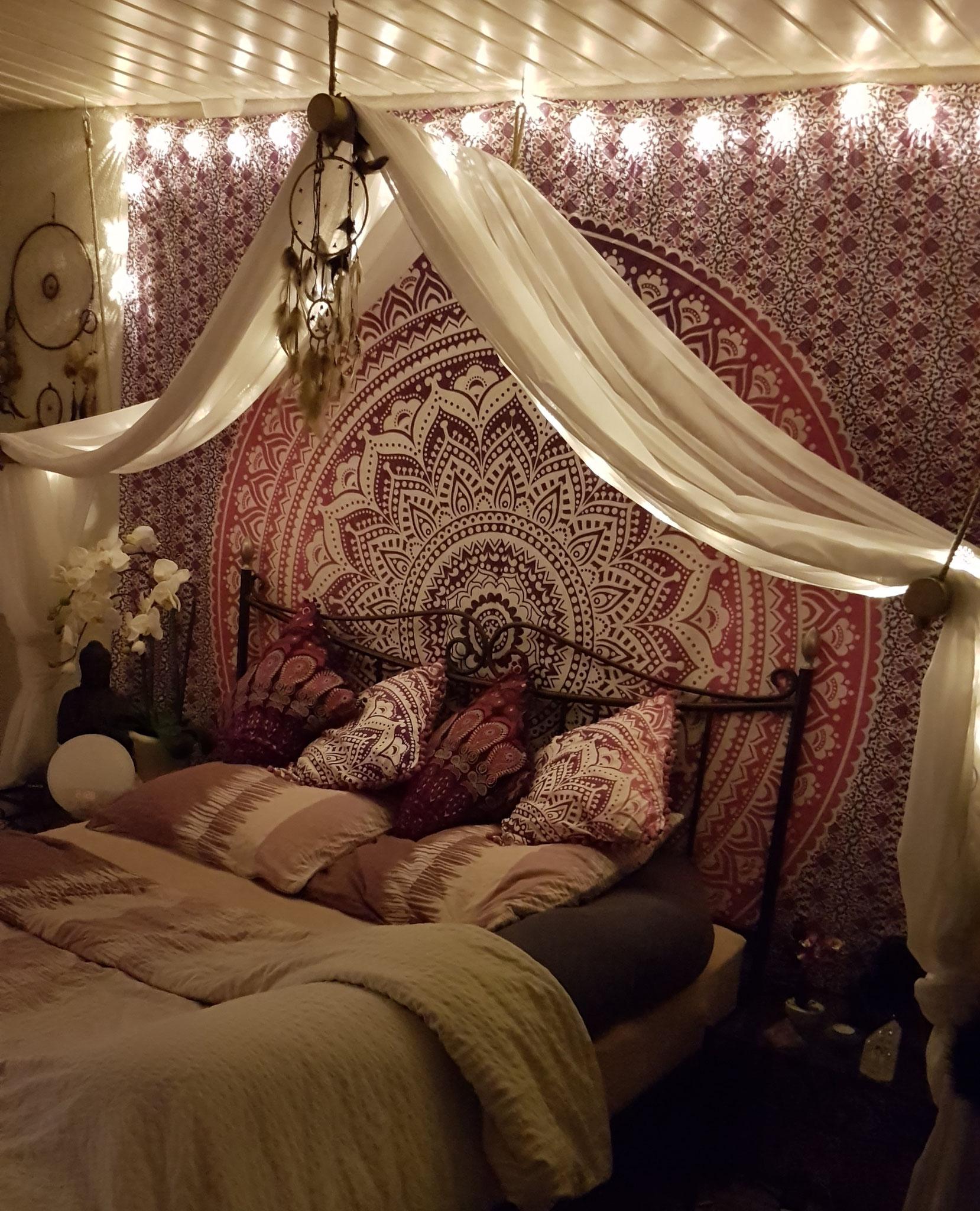 Zentrales Wandtuch mit Dekoschal und Lichterketten über dem Bett