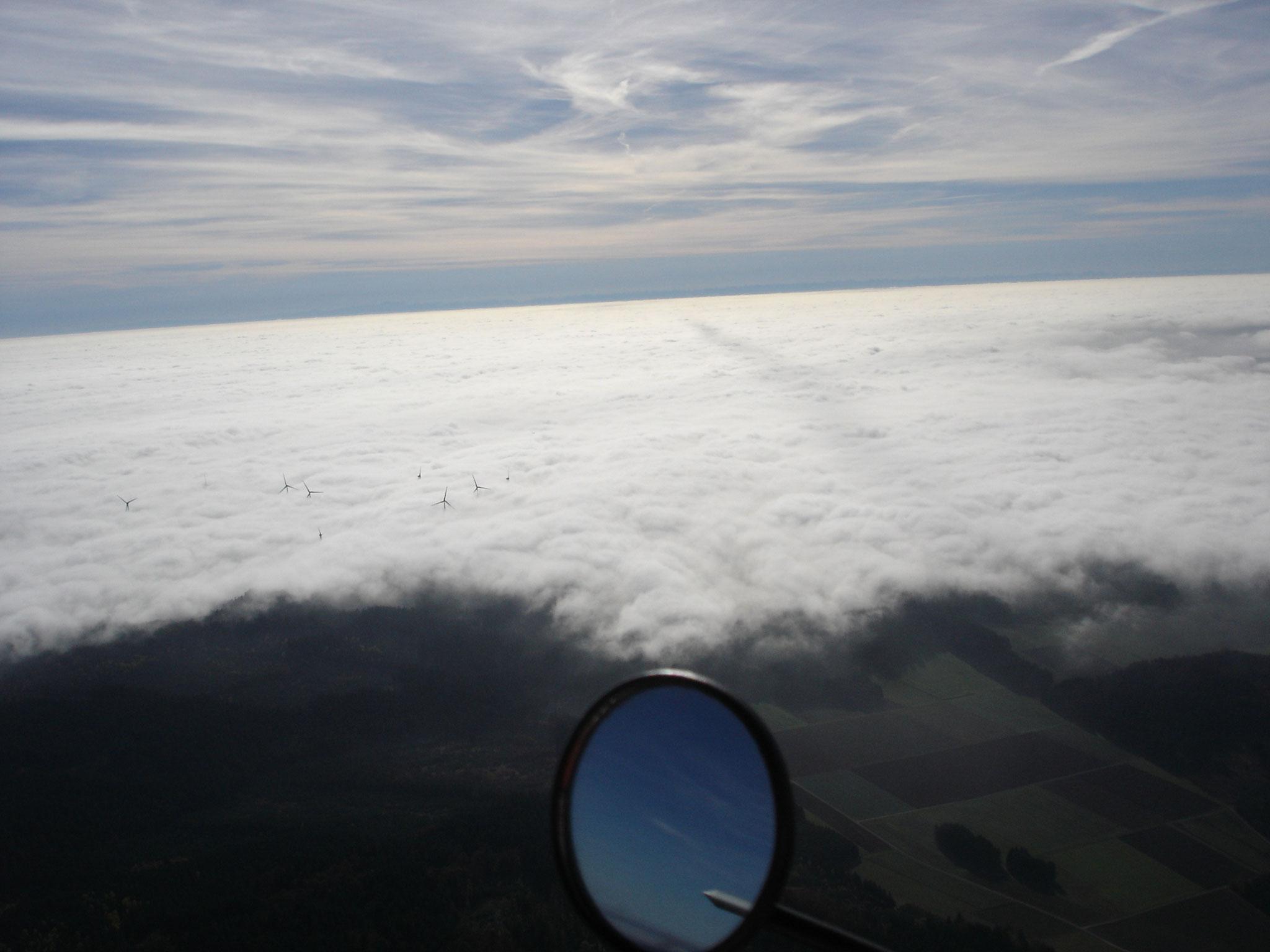 Windkraftrotoren über der Wolkendecke