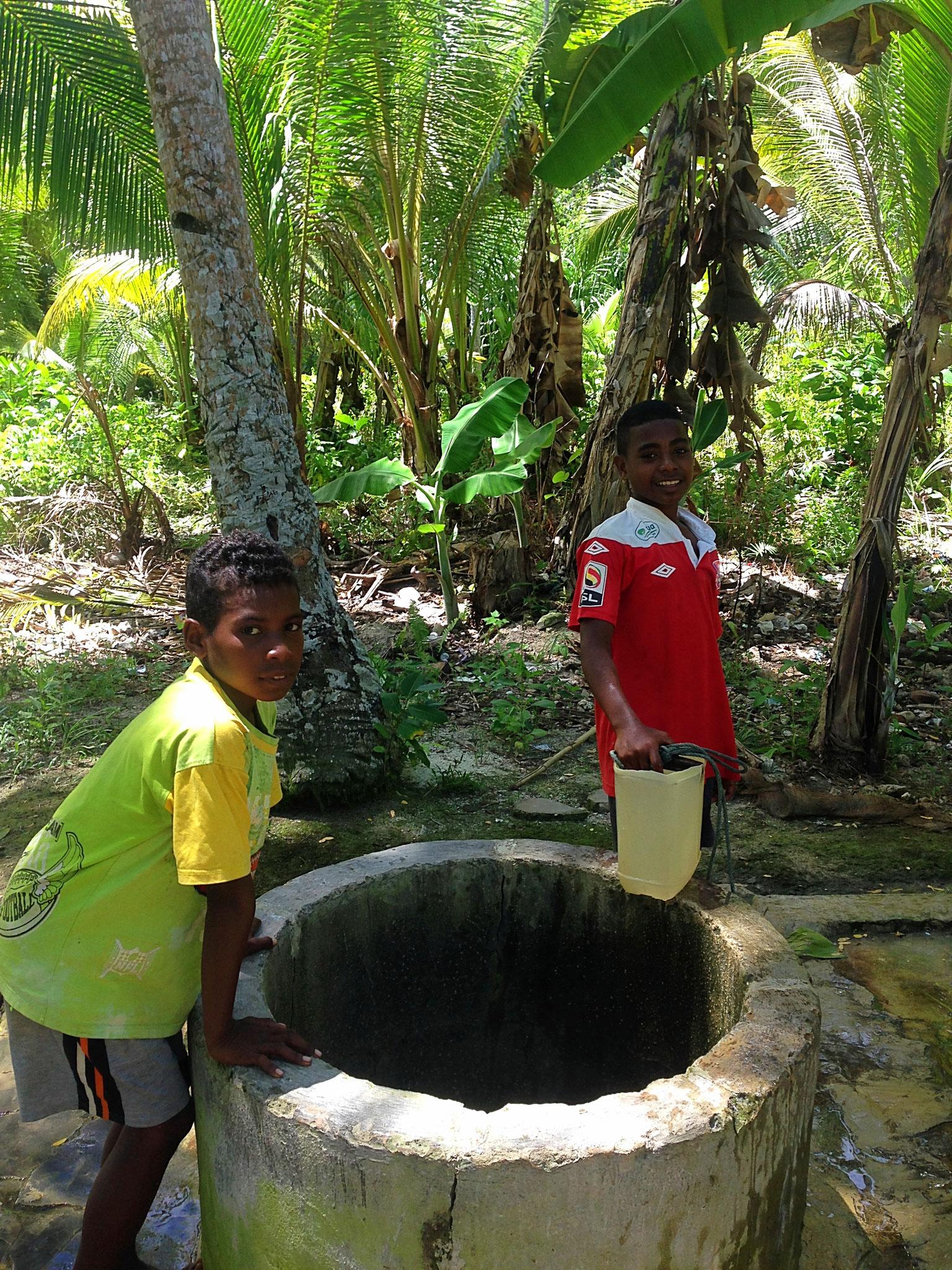 Kein fliessend Wasser - hier erfrischen sich zwei Jungen an einem Wasserloch