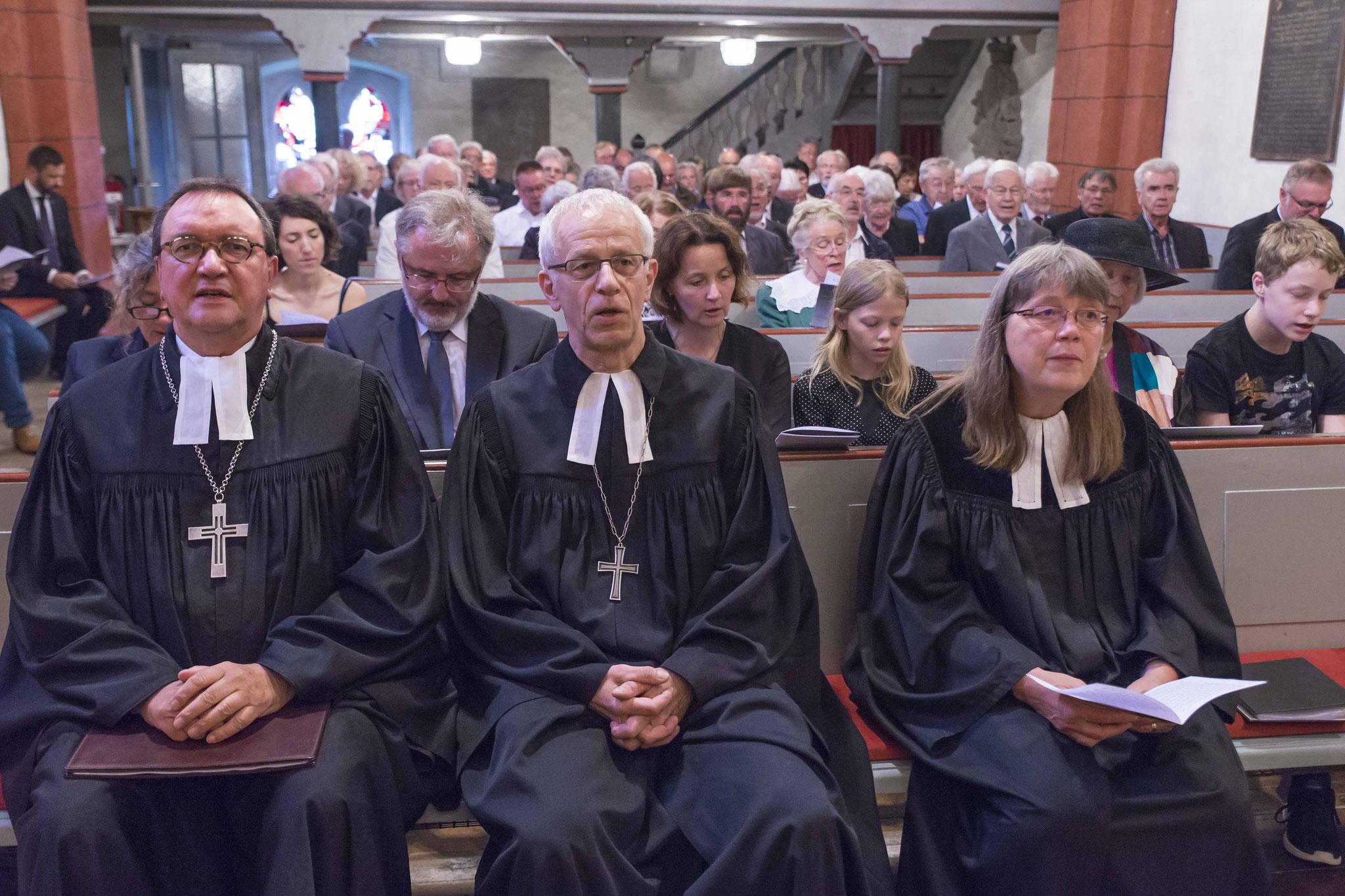 Bischof Prof. Dr. Martin Hein, Propst Helmut Wöllenstein, Pfarrerin Barbara Grenz. Dahinter Angehörige und Gottesdienstbesucher