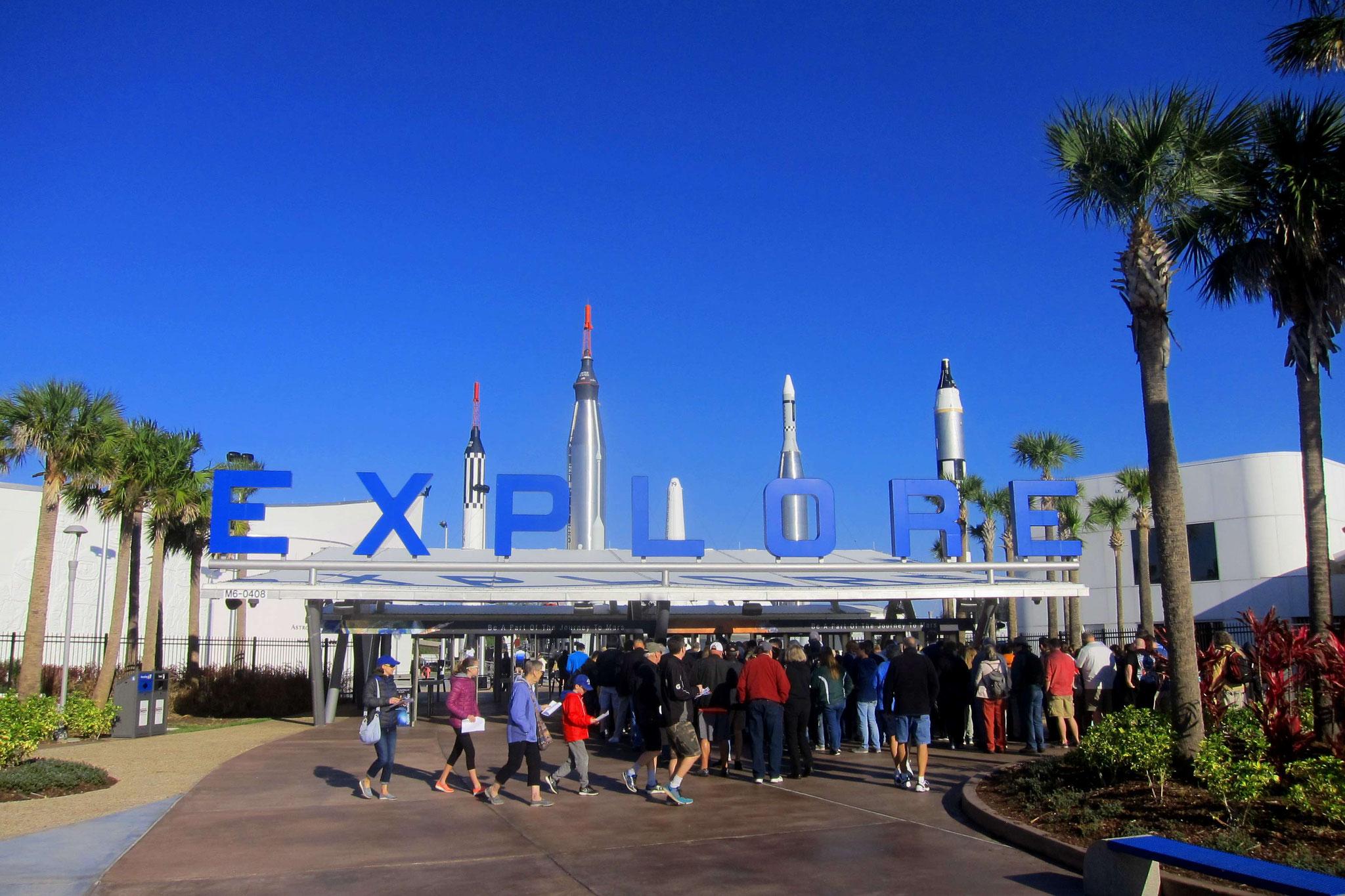 """Eingang des Kennedy Space Centers mit Raketen aus dem """"Raketen-Garten"""" im Hintergrund"""