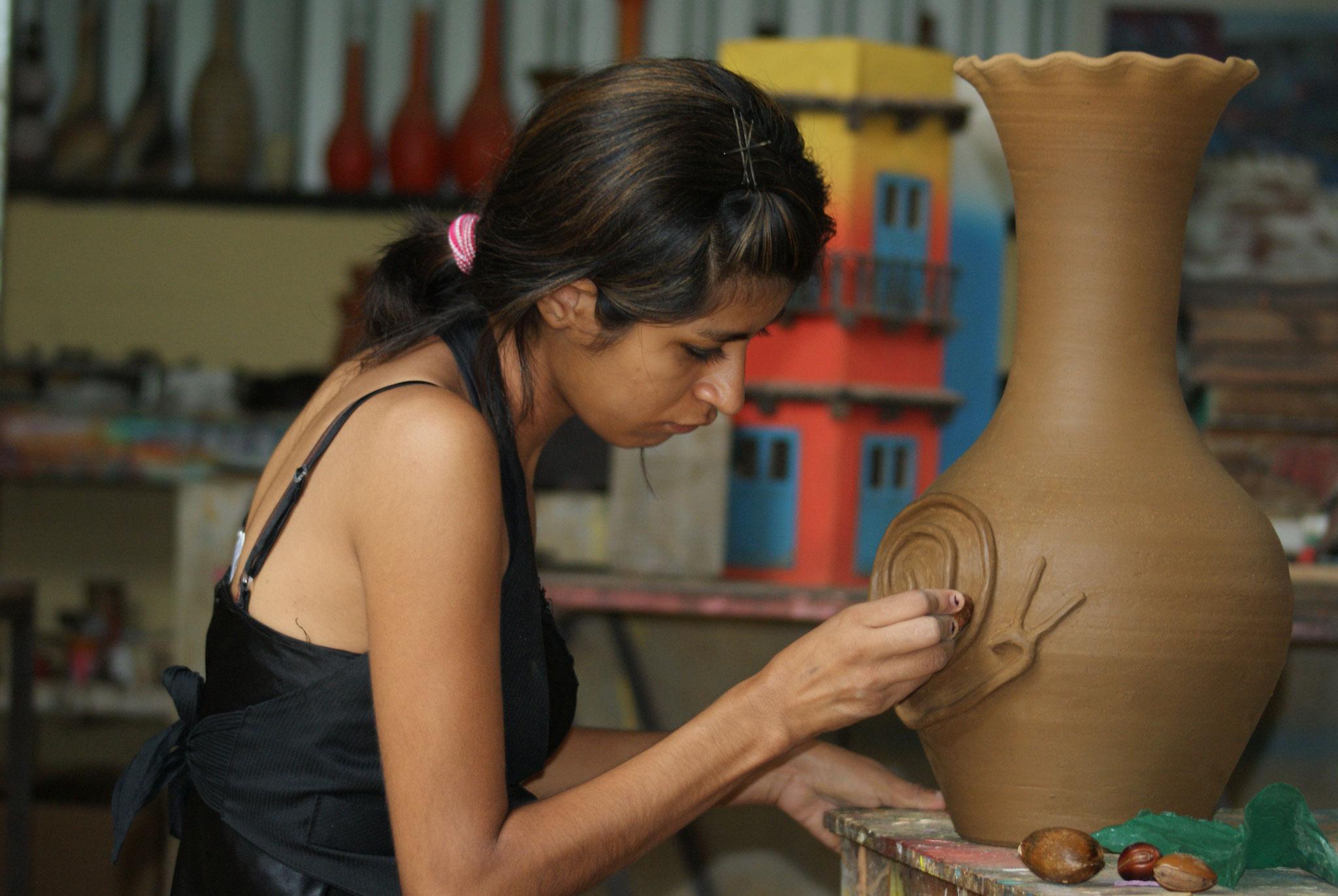 Eine junge Frau stellt Keramiken für ihr eigenes Geschäft her