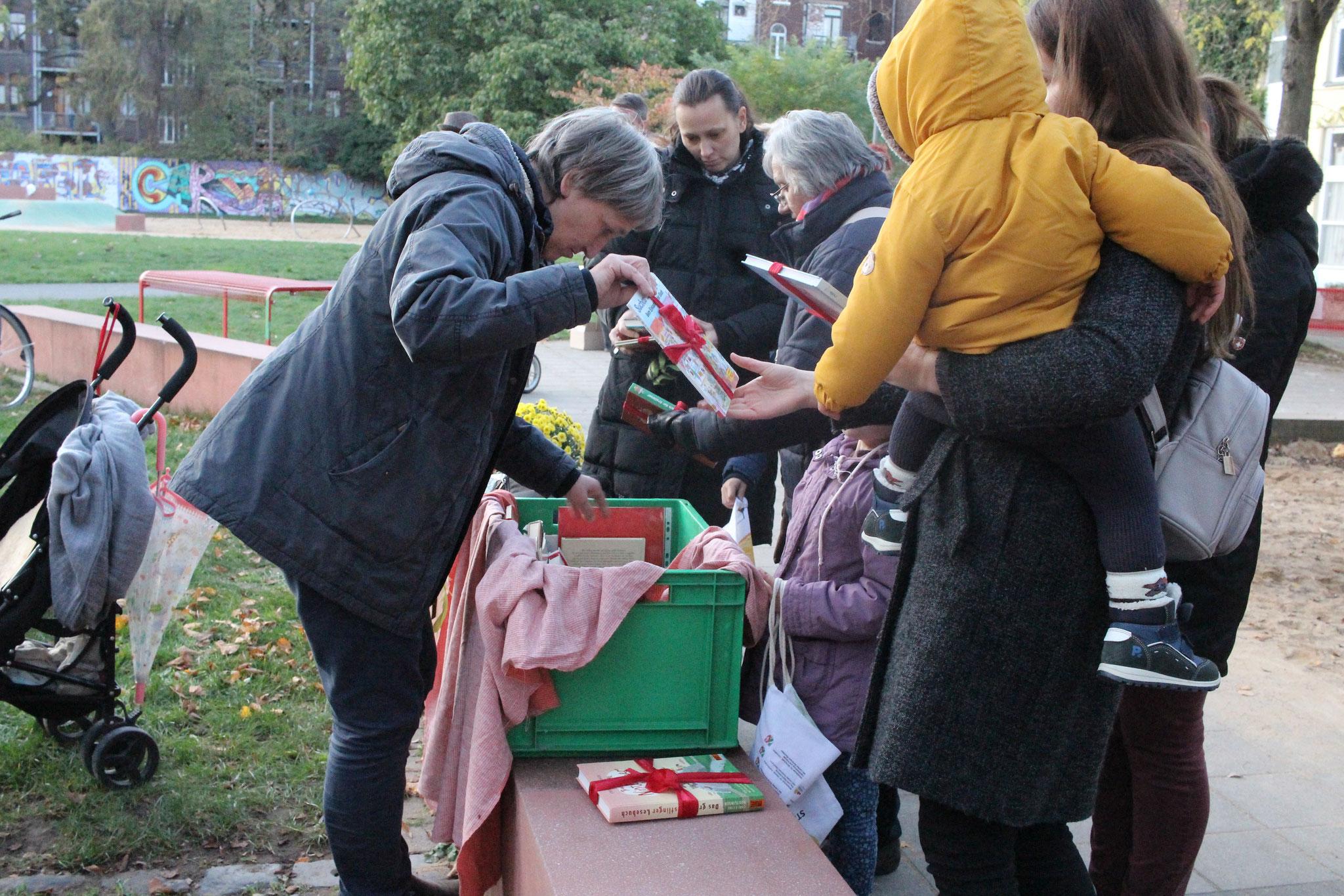 Gabi Schönau von der nachbarschaft köln-mülheim-nord e. V. gibt die schön verpackten Bücher an die Kinder aus.