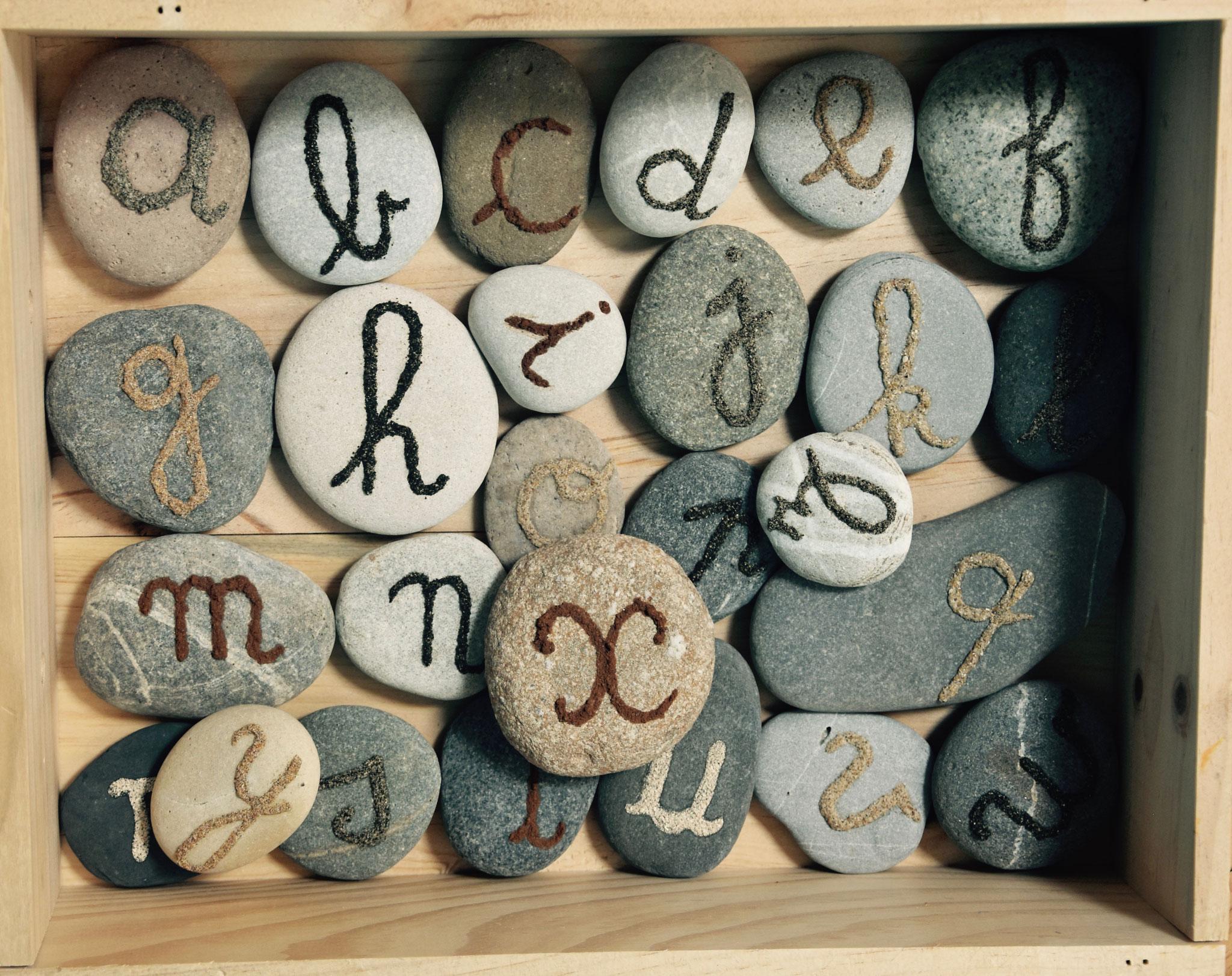 alphabet paléothique, galets avec écriture de sable, 177 euros ou 7 euros le galet
