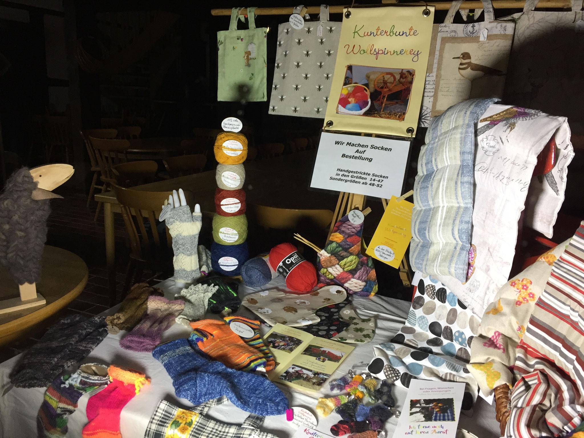 Blick in ein Handarbeits-Dorfhausfenster mit Wolle, selbst gestrickten Socken und Genähtem