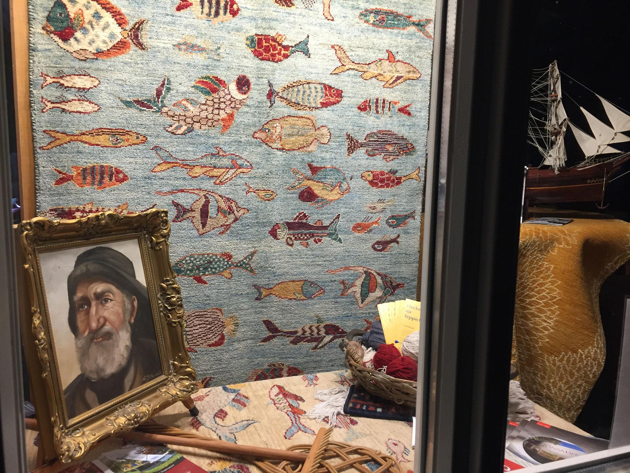 Blick in ein maritimes Dorfhausfenster mit goldgerahmtem Ölbild eines Fischers und Teppichen mit Fisch-Muster
