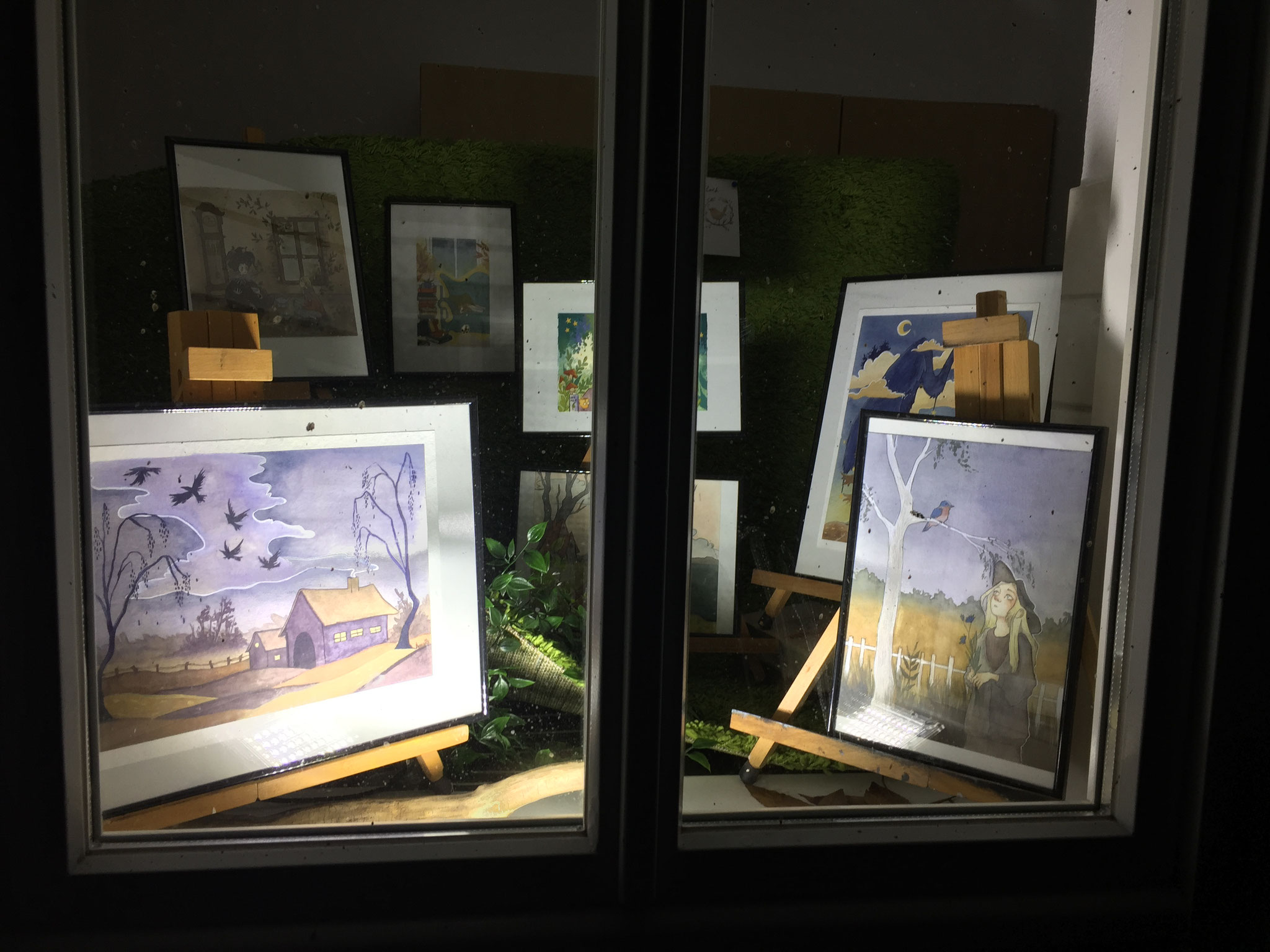 Blick in ein künstlerisches Dorfhausfenster mit verschiedenen gemalten und gerahmten Bildern