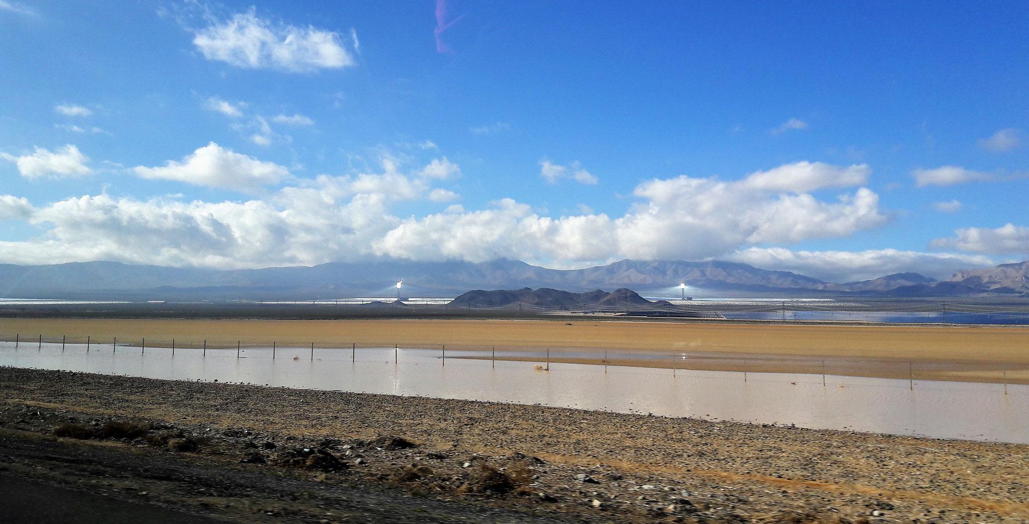 Alternative vom selben Tag wie das vorige Bild: in der Wüste steht im Winter manchmal Wasser. Und dahinter werden in der Ferne spannende Solar Experimente durchgeführt. Oder Aliens haben da ihre Basis. Es gibt nur einen Weg es herauszufinden.
