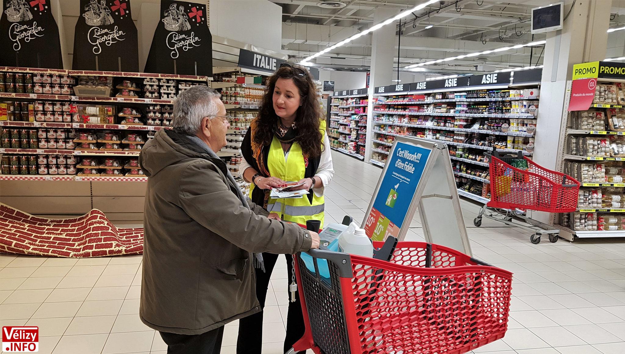 Virginie, bénévole ESV, explique l'opération « Un don, un sourire » à un client du magasin Auchan Vélizy.
