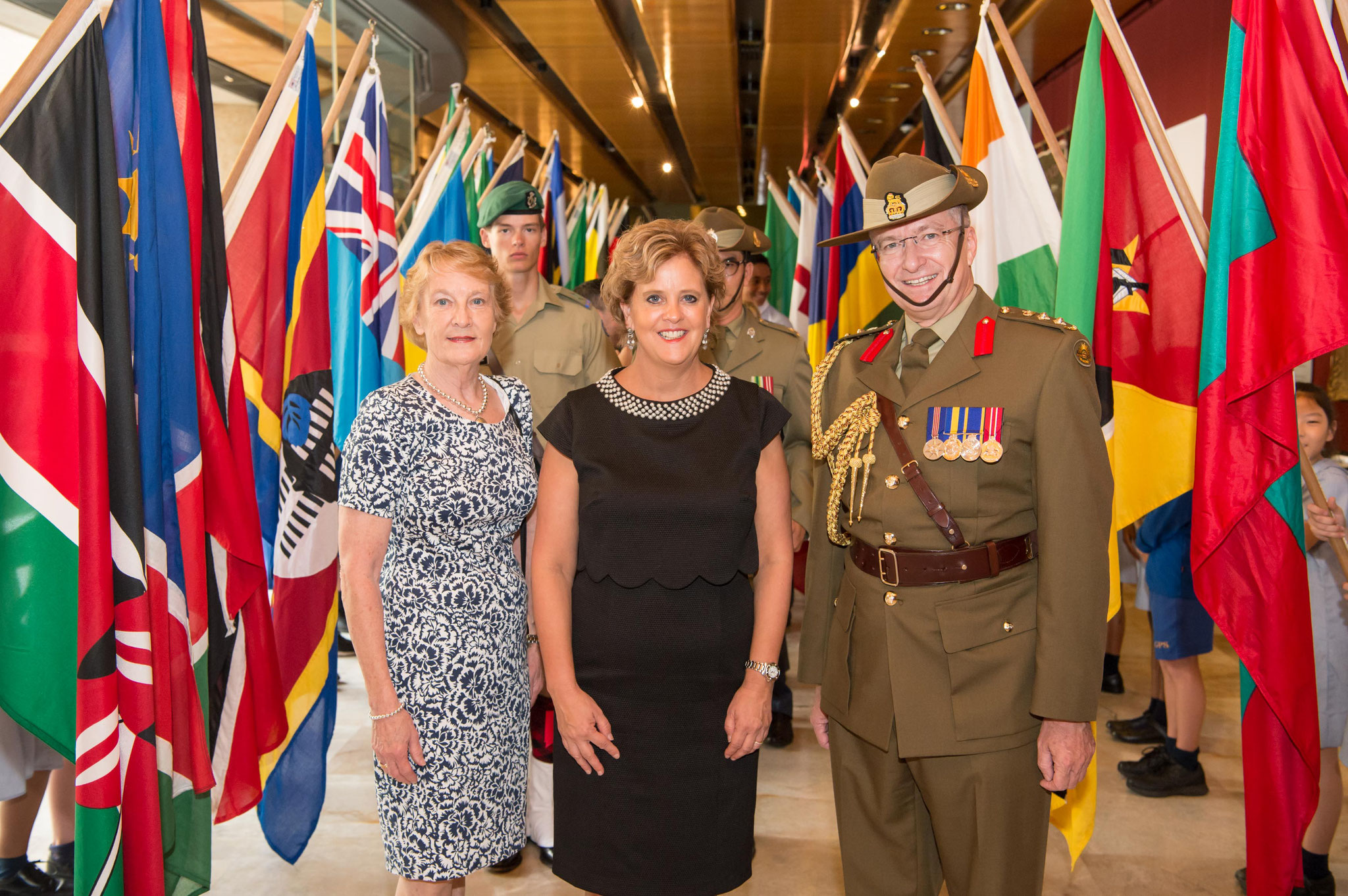Janet Stewart (left); Her Excellency CMG and Michael Miller RFD with the flags of the 54 Commonwealth of Nations flags