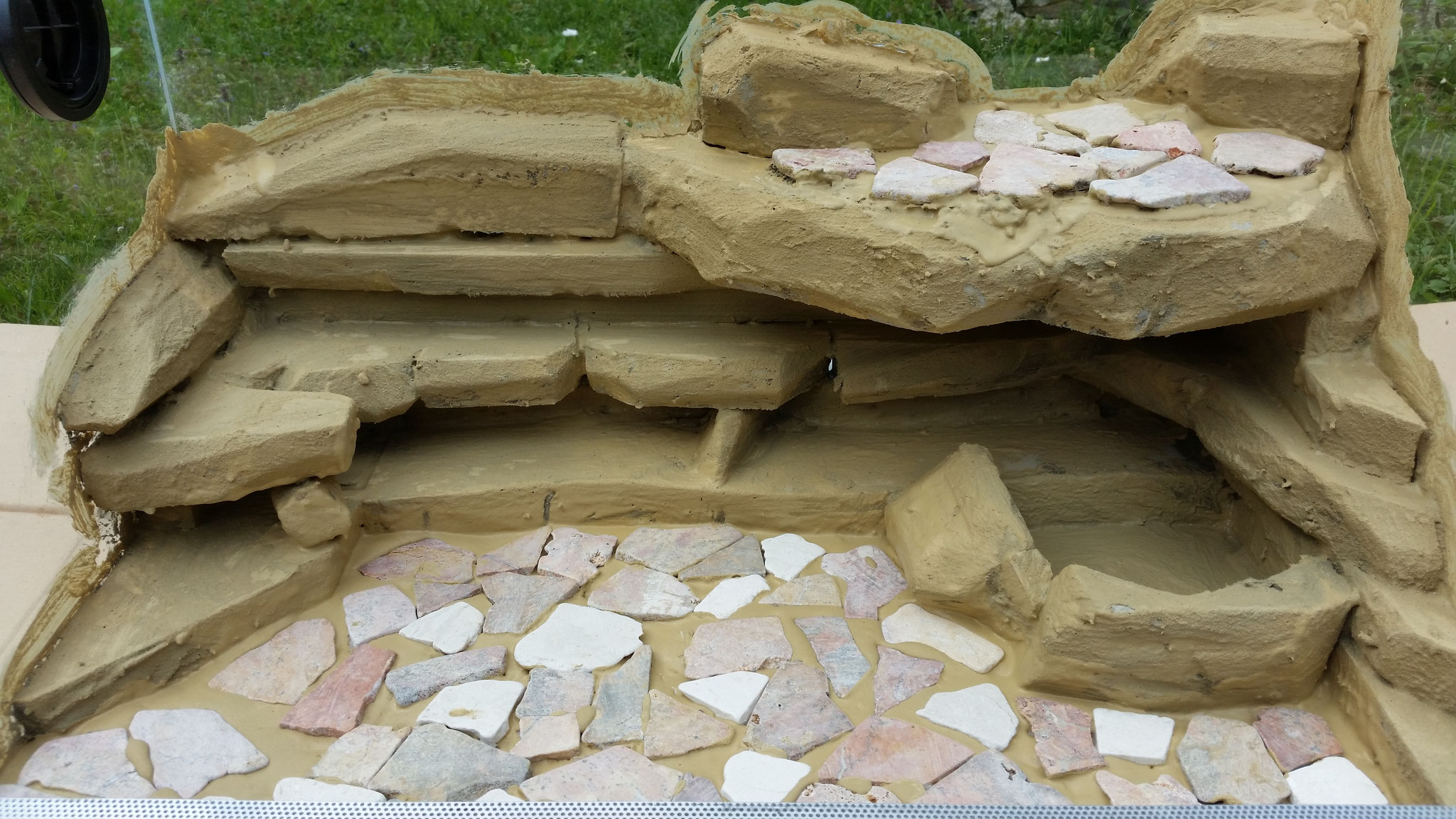 Bruchmosaik am Boden sowie am großen Felsvorsprung verlegen