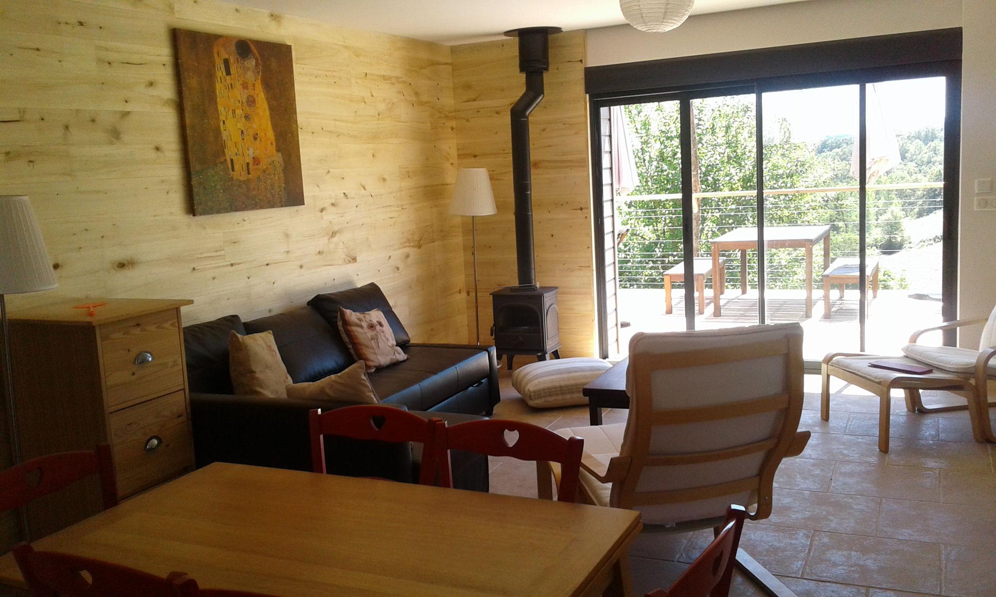le salon avec son canapé convertible et confortable, poêle à bois, et vue sur la terrasse.