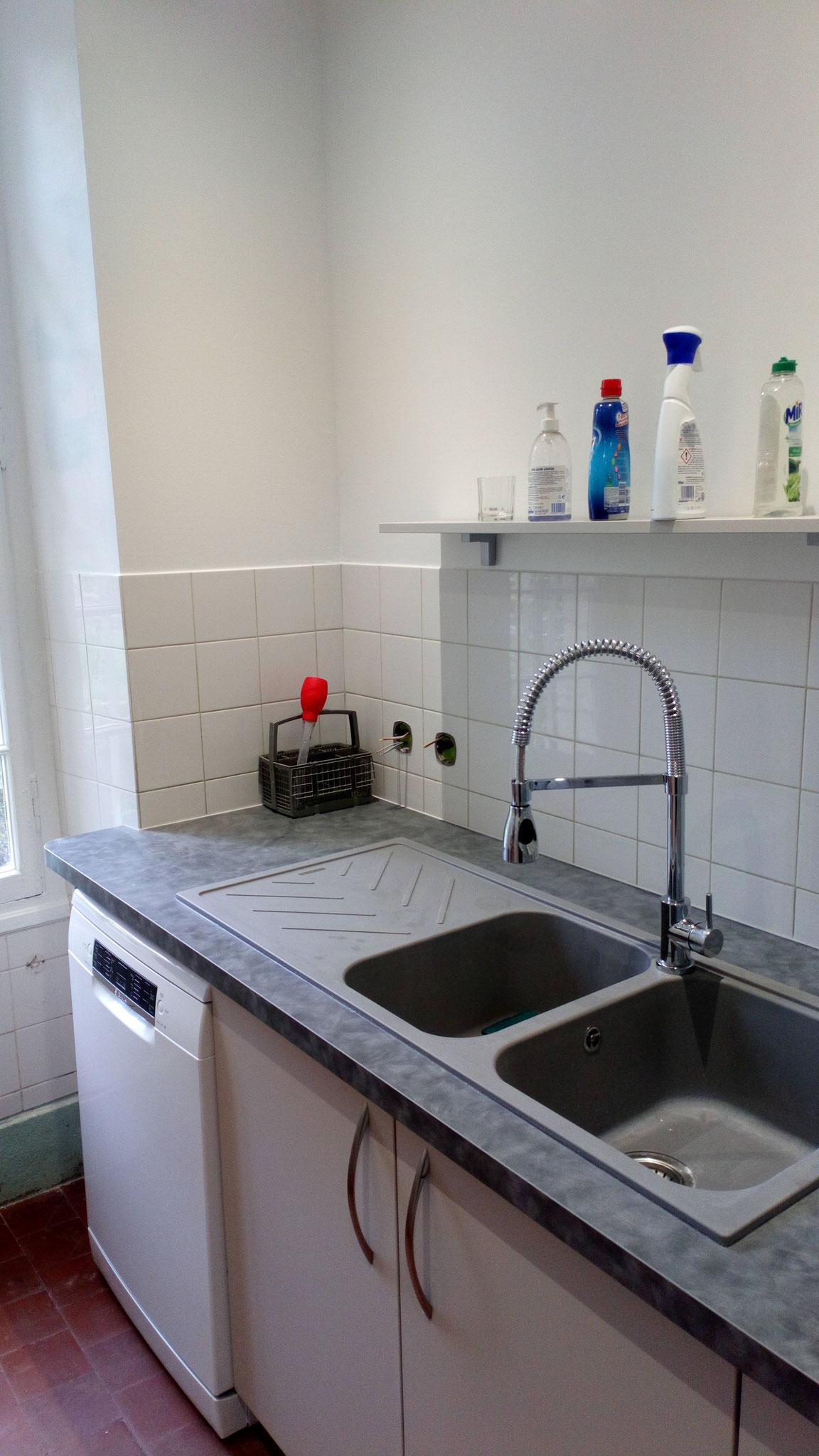 Lave-vaisselle en pose libre sous l'égouttoir de l'évier