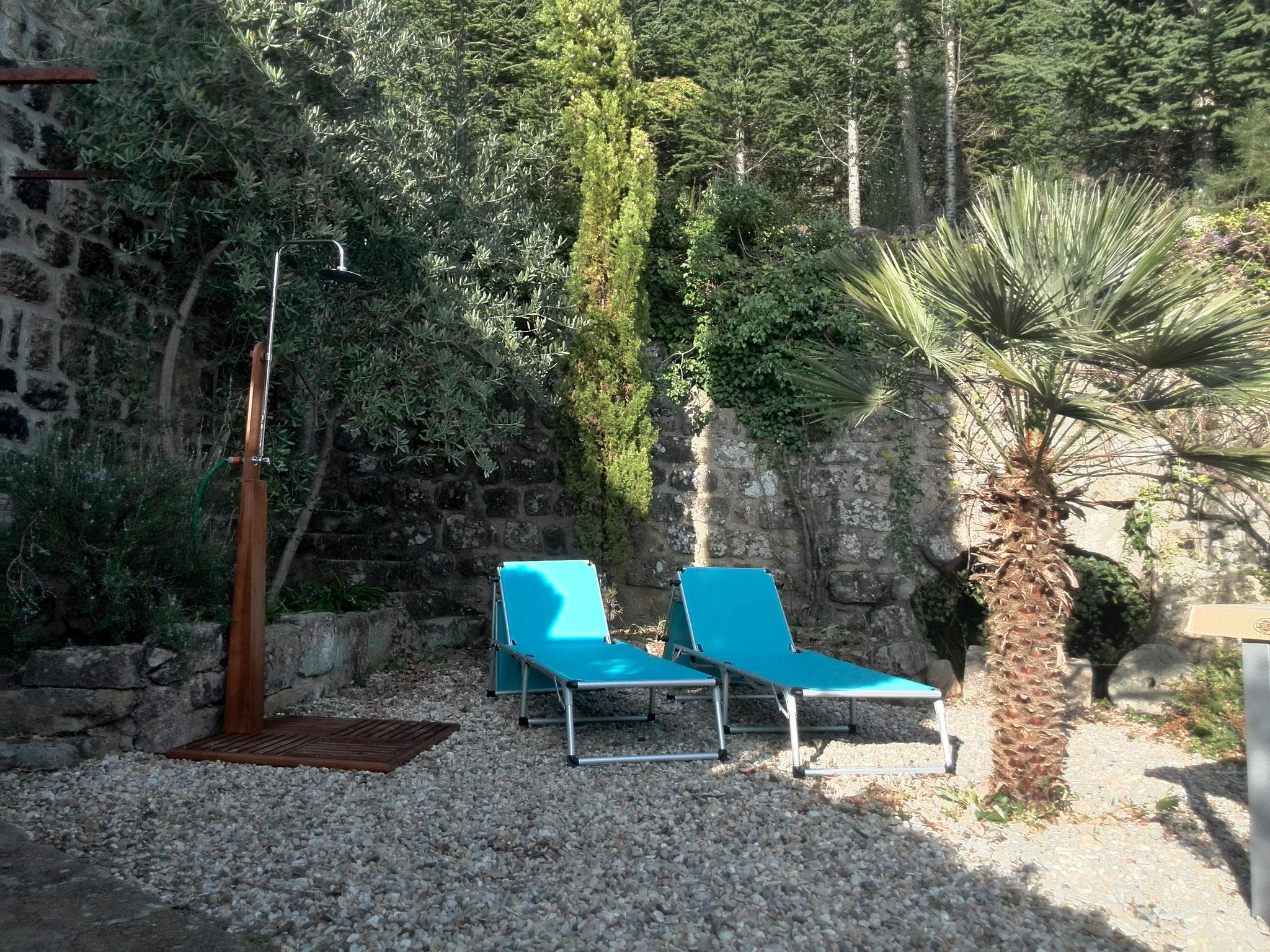 Außendusche und Sonnenliegen im Innenhof