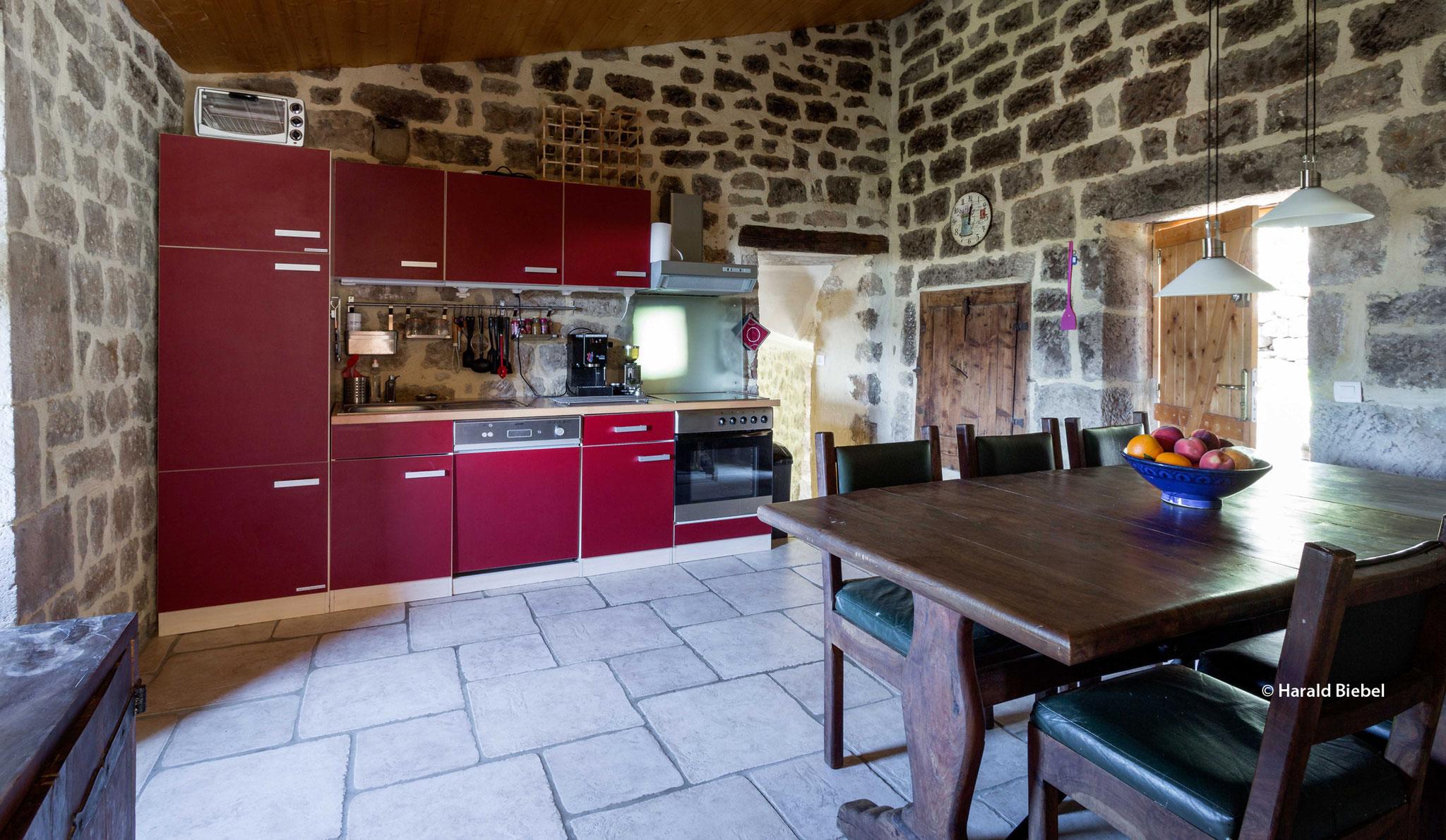 Küche mit großem Esstisch und kleiner Terrasse davor