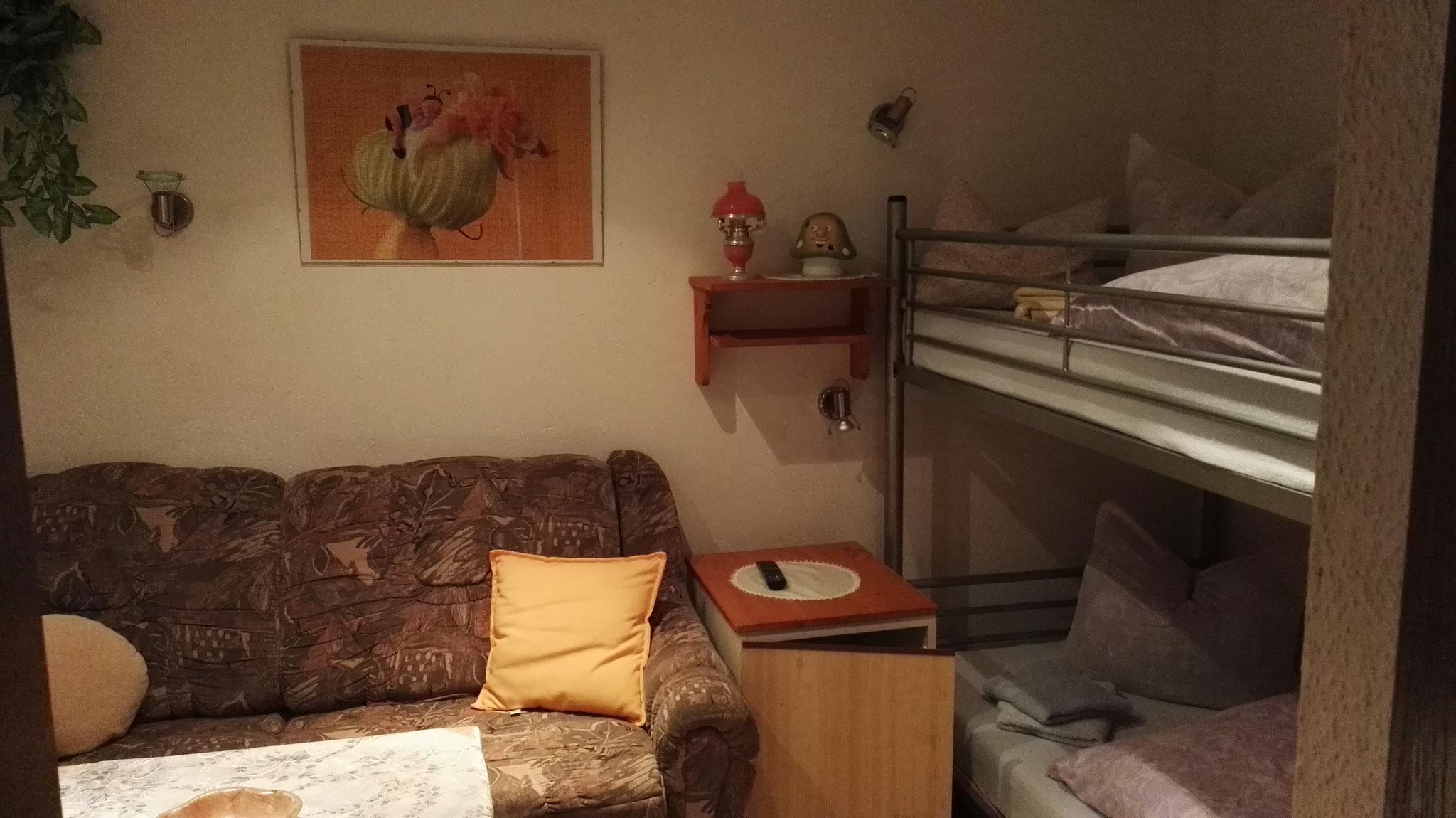 Das Zimmer im Erdgeschoß mit Doppelstockbett und Sofa, sowie einem Fernseher.