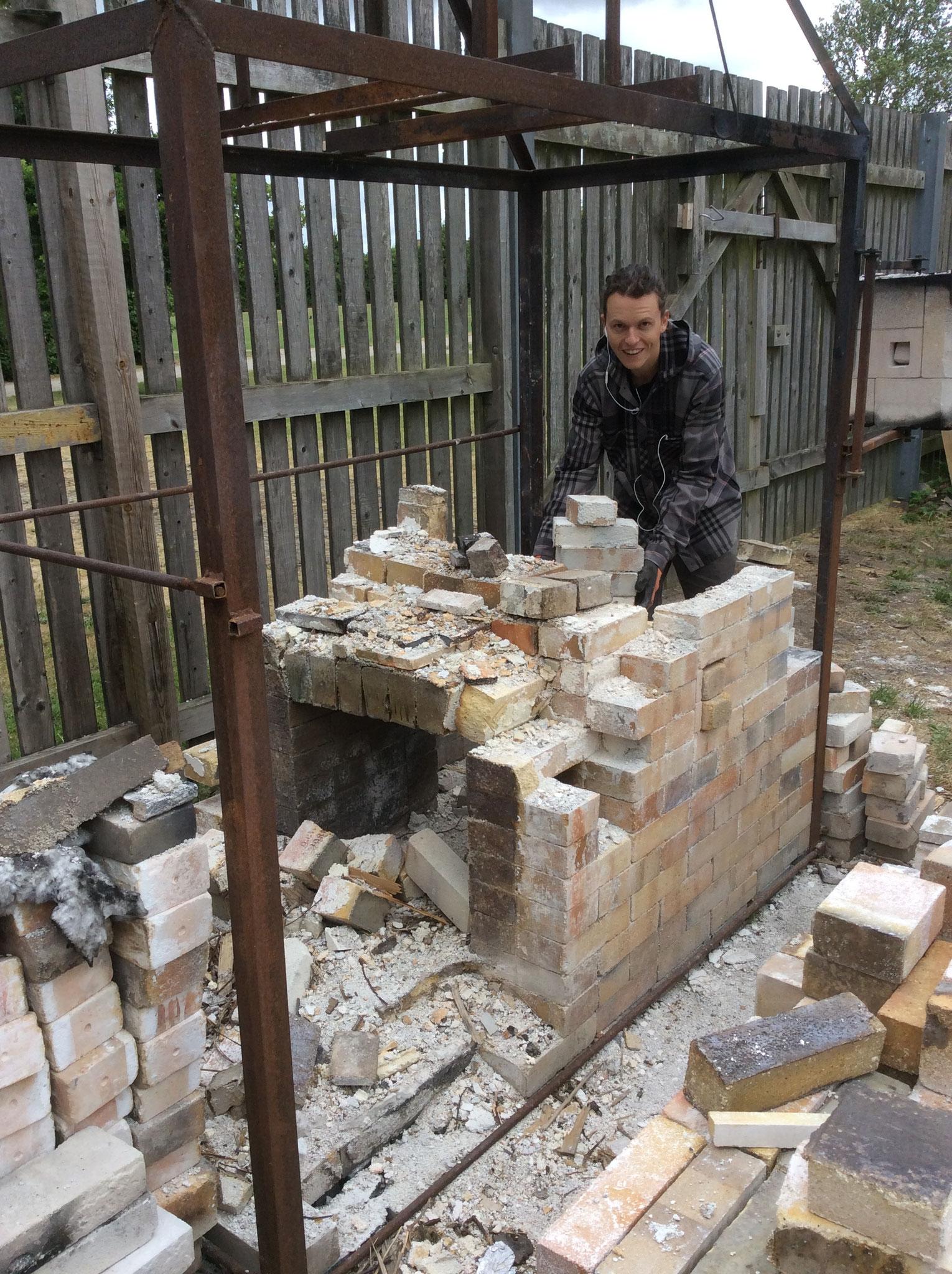 Brian Buckland aus der USA beim Aufbauen eines Holzbrandofens