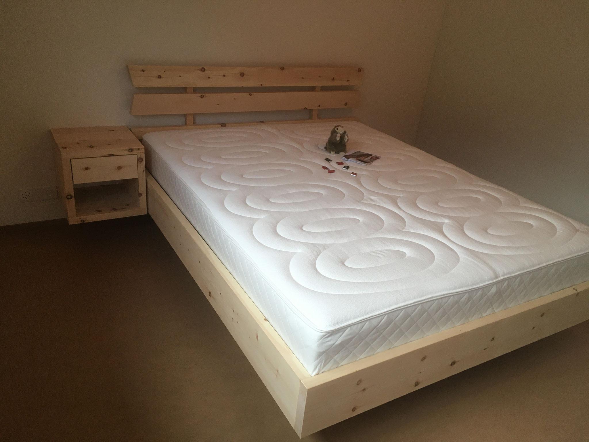 Arven Bett mit passendem Nachttischli und dem kompakten Designa Bettinhalt von Hüsler Nest