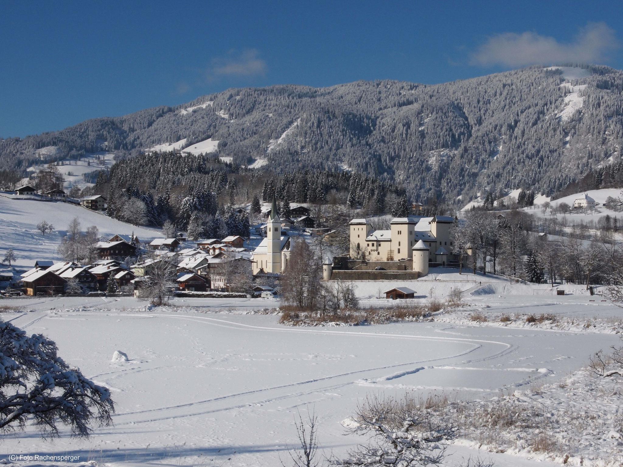 Goldegg mit verschneitem See im Vordergrund