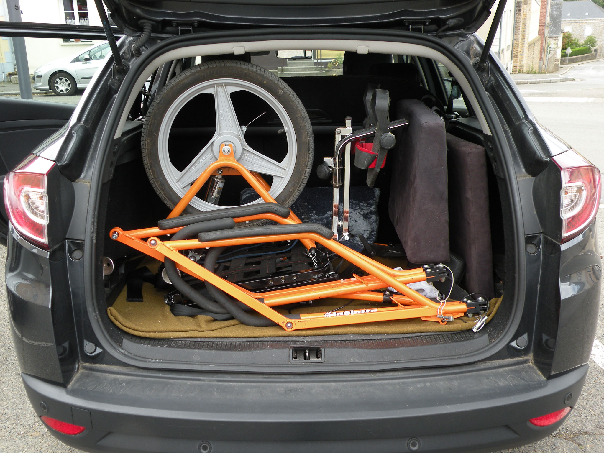 """La Joëlette est pliée. Elle est positionnée dans le coffre d'un véhicule de tourisme type """"break"""""""