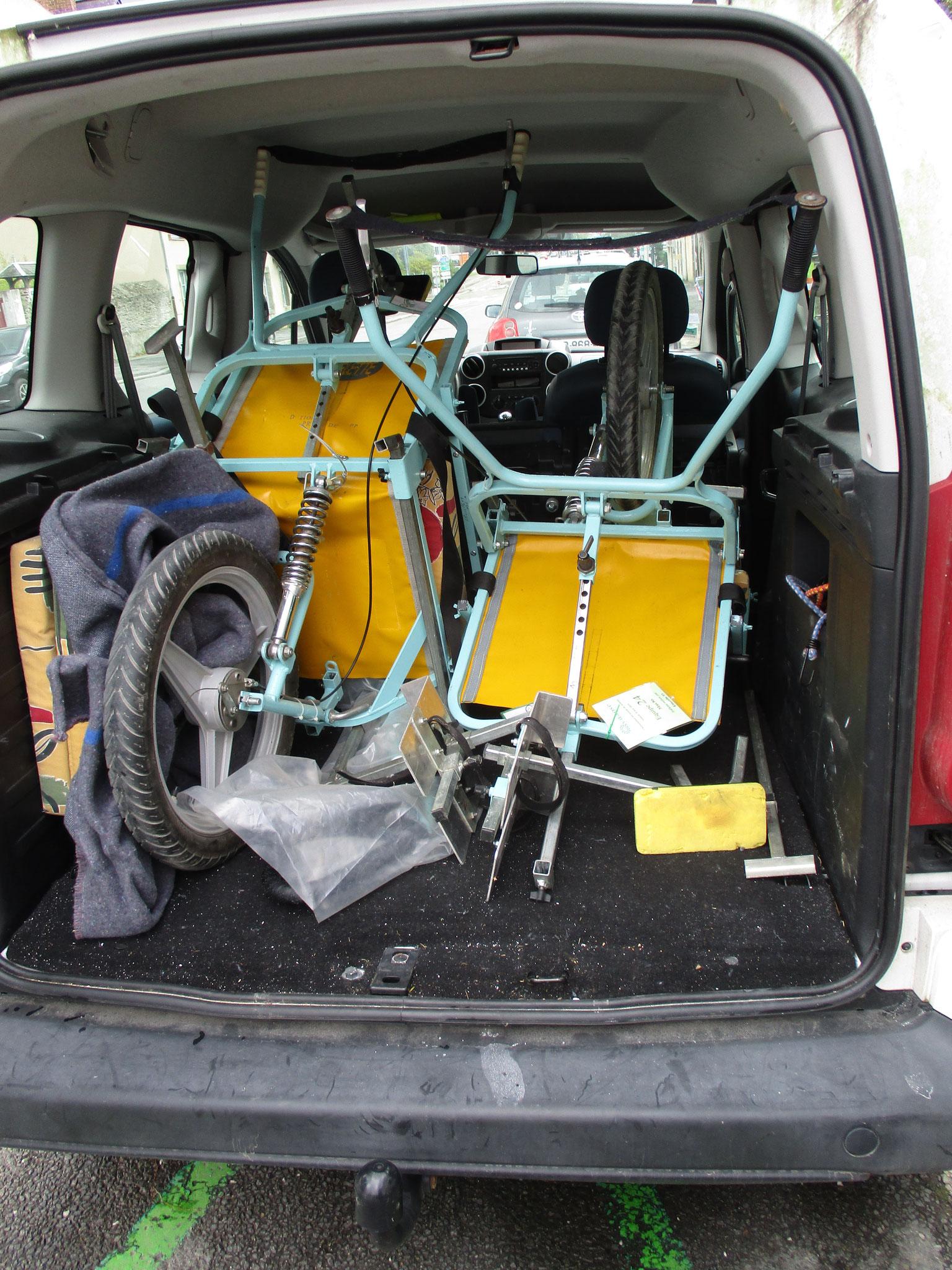 """2 Joëlettes (non pliées) dans un véhicule type """"Kangoo"""" vue de l'arrière du véhicule"""