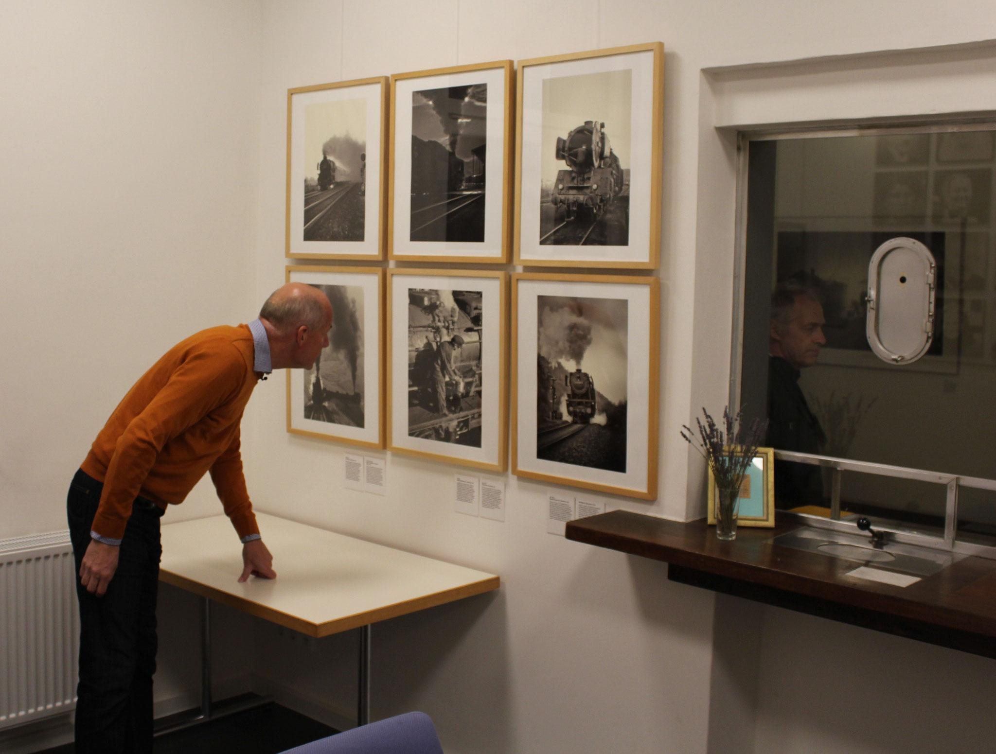 Gerd Lübbering wirft vor Ausstellungsbeginn einen letzten prüfenden Blick auf die ausgestellten Bilder.