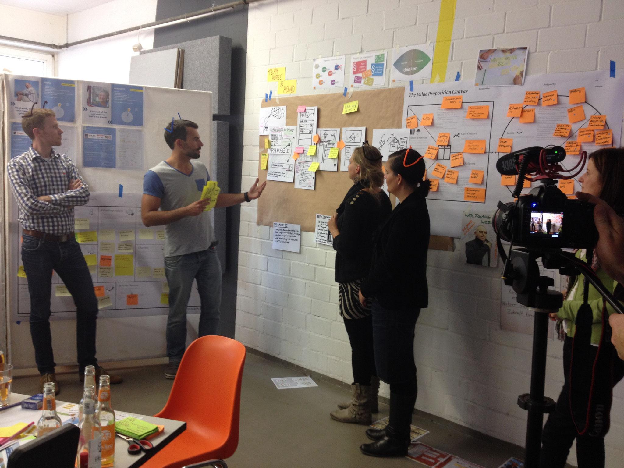 Das Team diskutiert die Entwürfe und bildet sie auf dem Werkzeug Value Proposition Canvas ab.