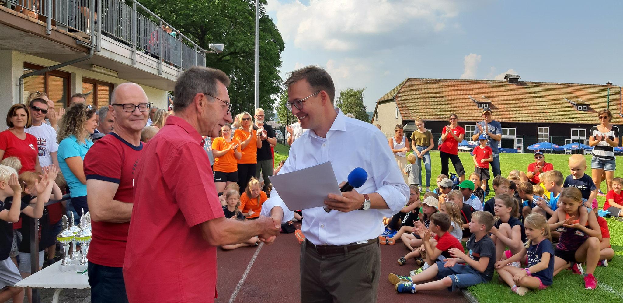 Erster Kreisbeigeordneter Frederik Schmitt übergibt den Förderbescheid für das Fest.