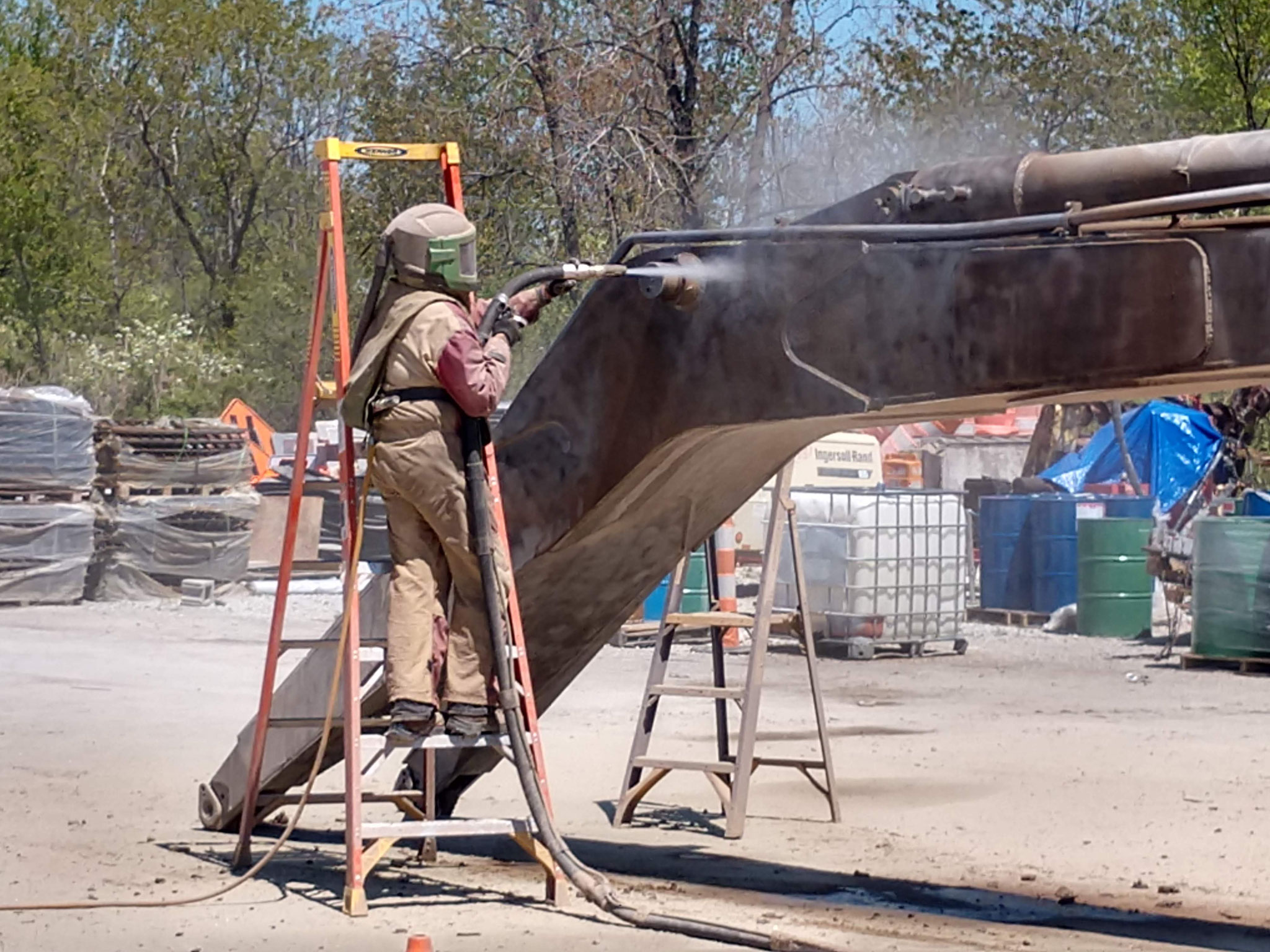 After removing the boom, a mobile sandblaster prepared the steel for painting